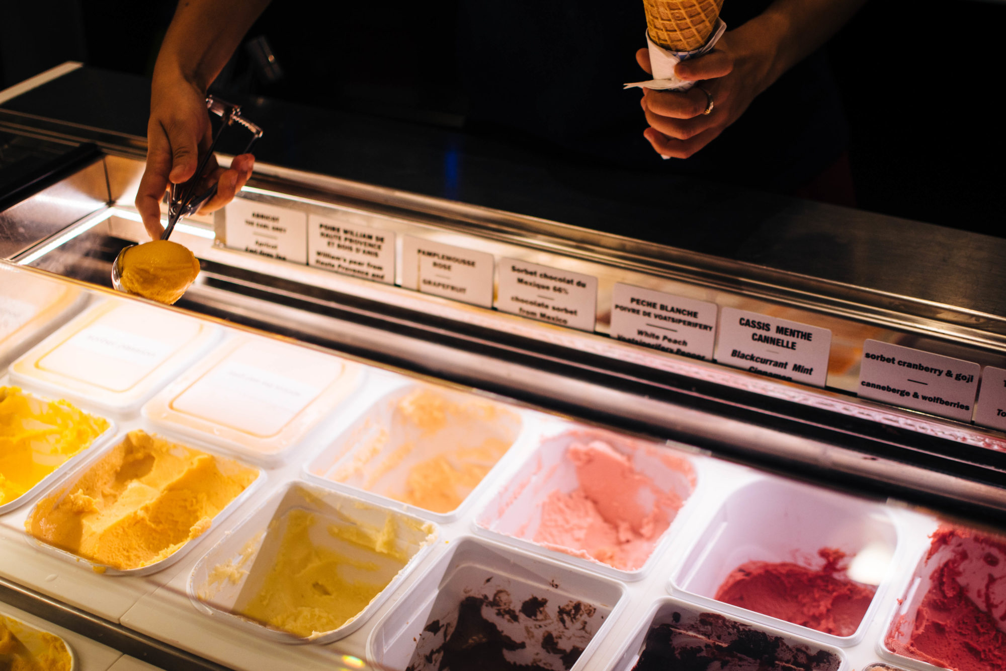 The ice cream counter at Pozzeto ice cream shop in Paris with a vendor scooping out the flavors into a cone.