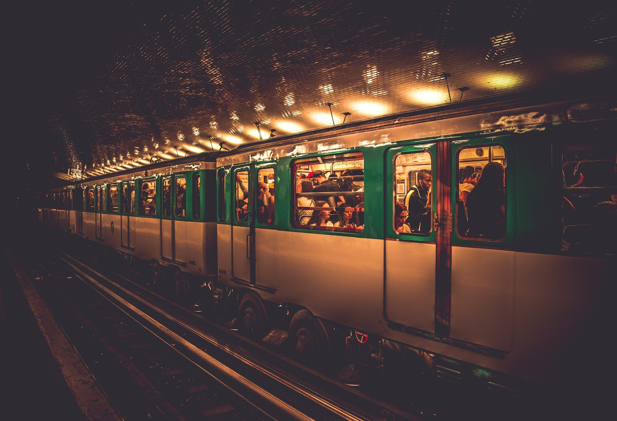 A metro pulling in at a metro station in Paris with passengers seen through the windows.