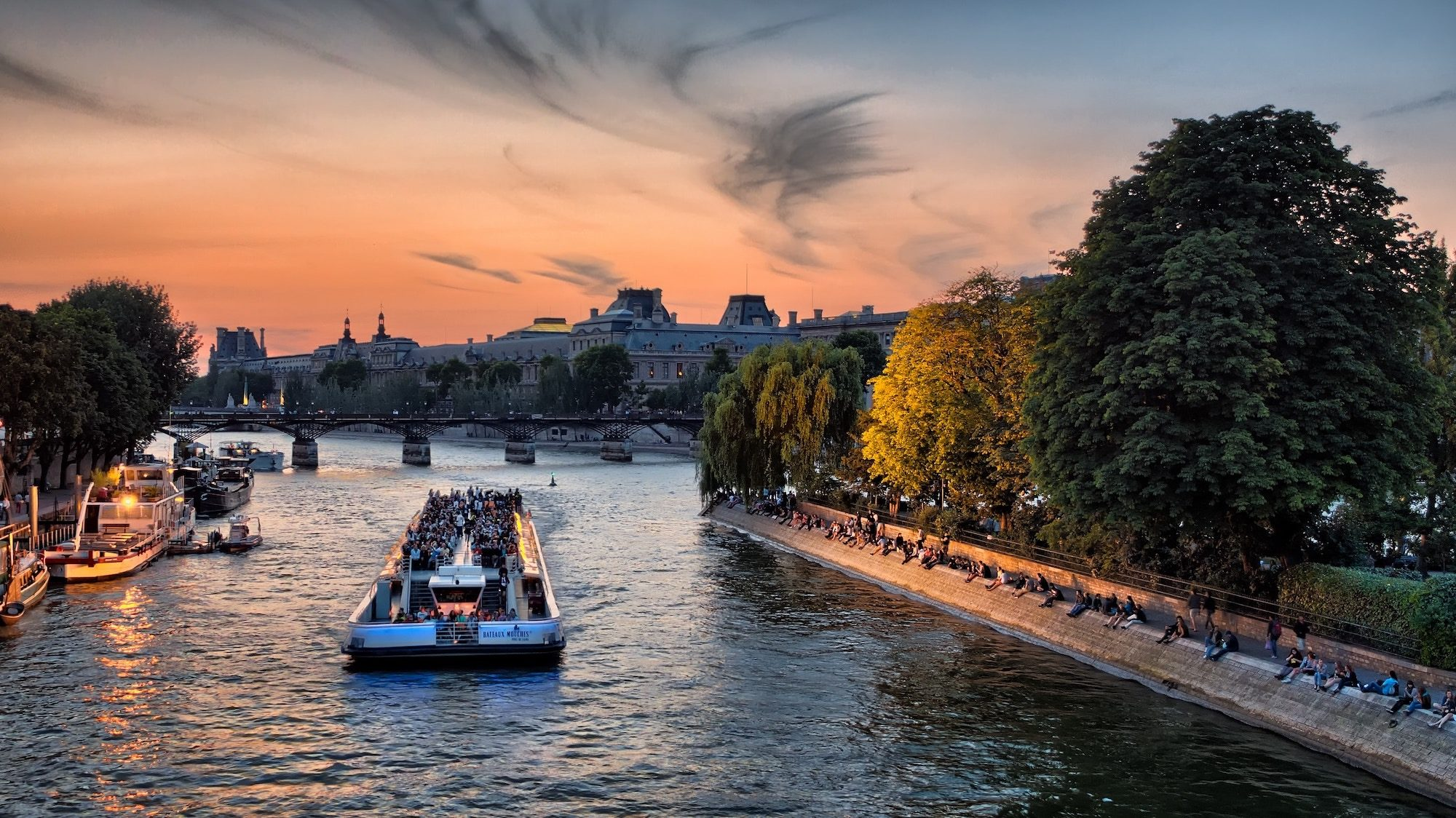 A view of the River Seine at sunset and a boat is sailing on the water, everything around it is golden from the sunlight.