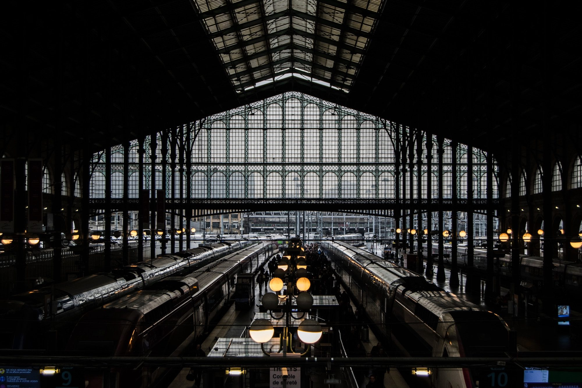 A shadowed view of trains waiting at the platforms of the Gare du station with its Art nouveau glass and iron structure.
