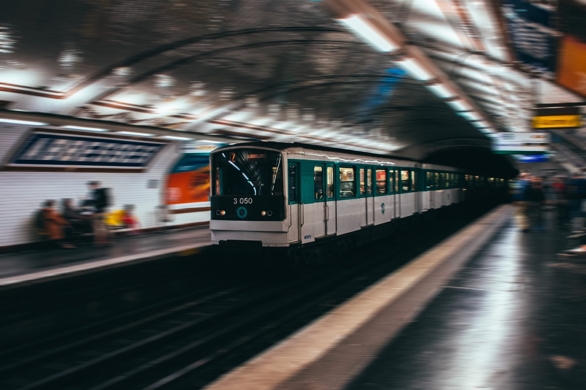 A metro train pulling in at Abbesses metro station. The train is the only thing in focus while the rest of the image is blurry.