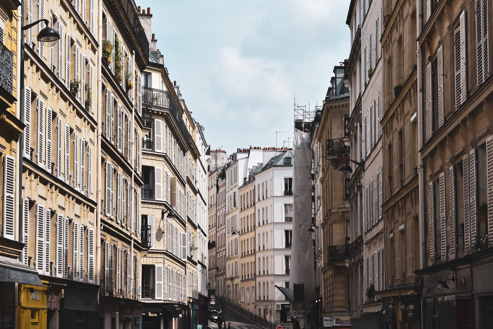 A view of white stone buildings with shutters lined up on both sides of a Paris street.
