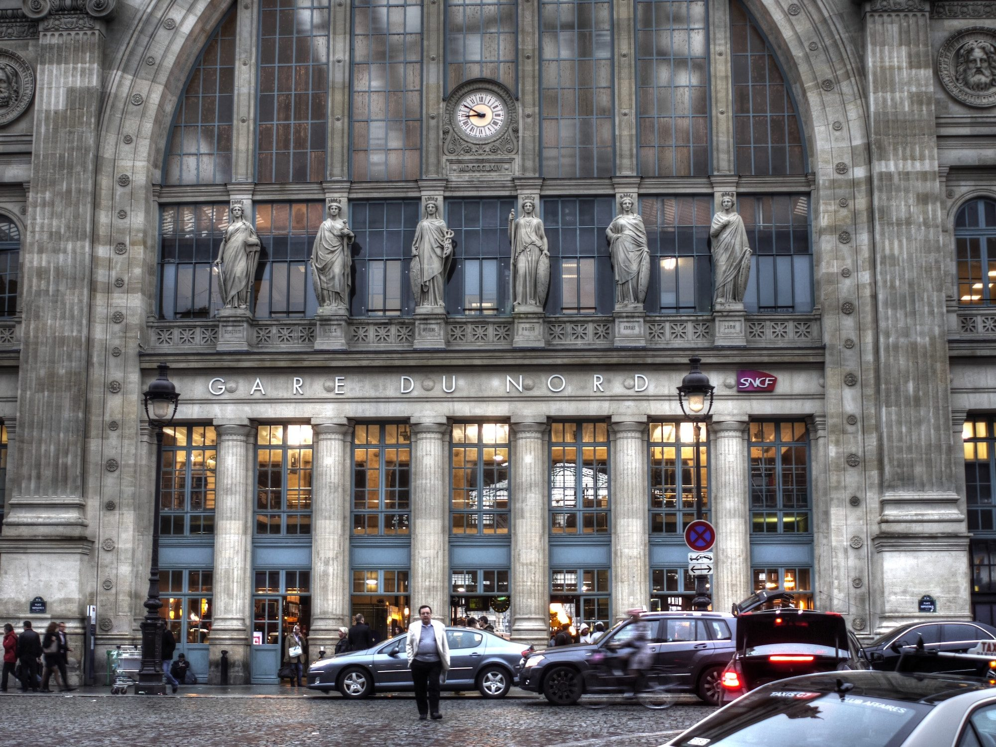 The beautiful statues lined up above the Gare du Nord's main entrance in Paris on a grey rainy day with a taxi driver standing in the foreground.