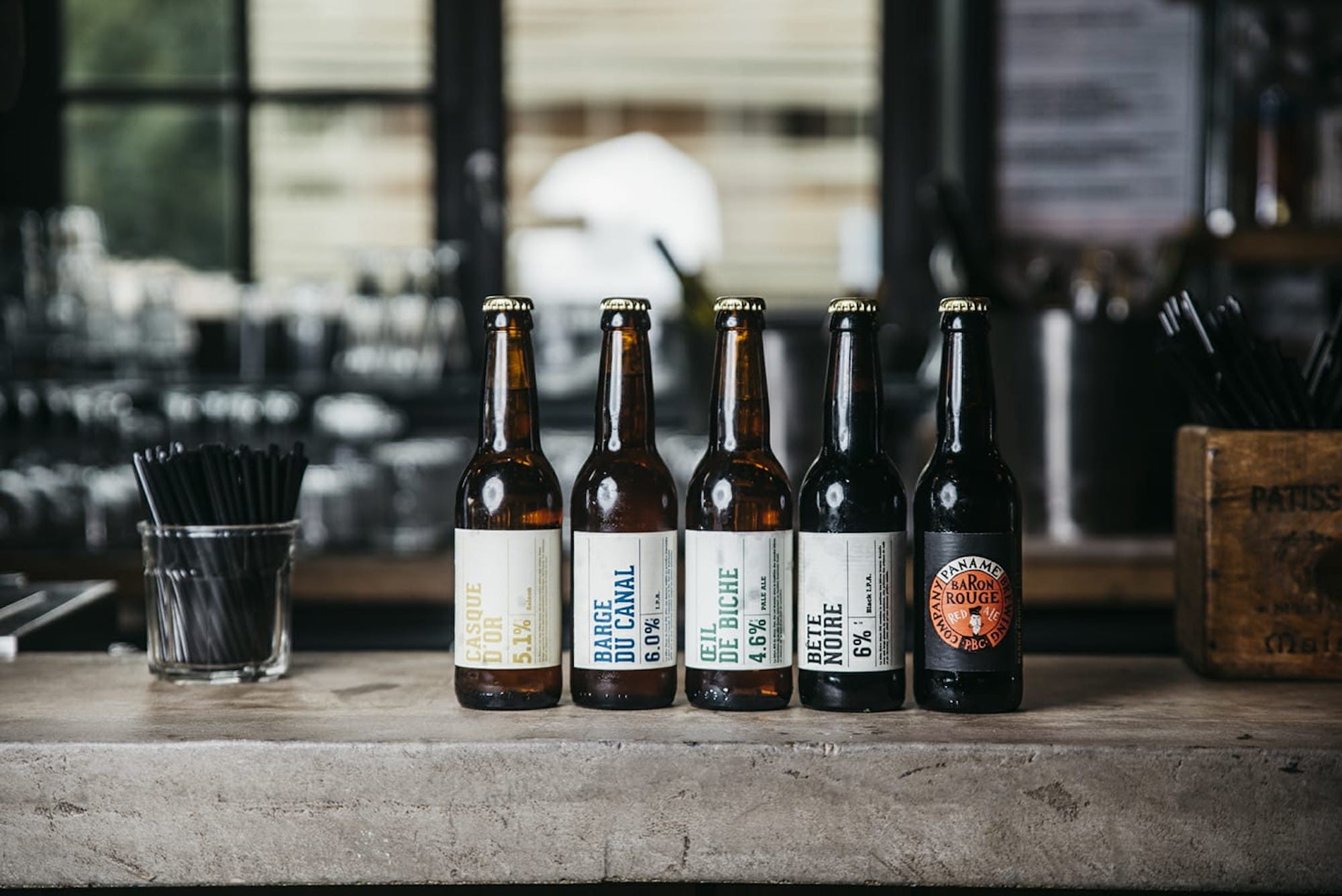 Five artisanal beers lined up on a bar counter