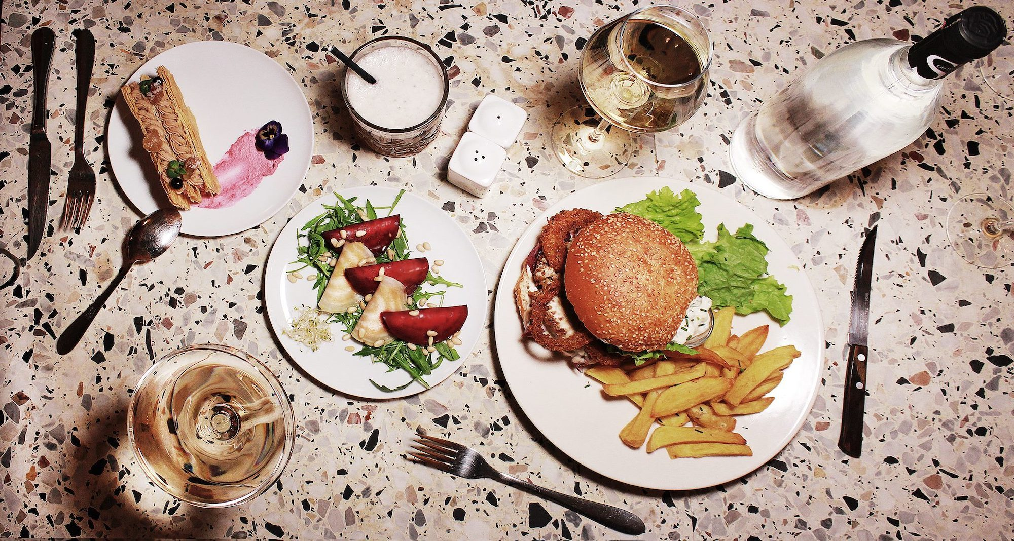 A spread of vegan burger with homemade fries and a starter of beetroot on a terrazzo table at BrEAThe restaurant in Paris.