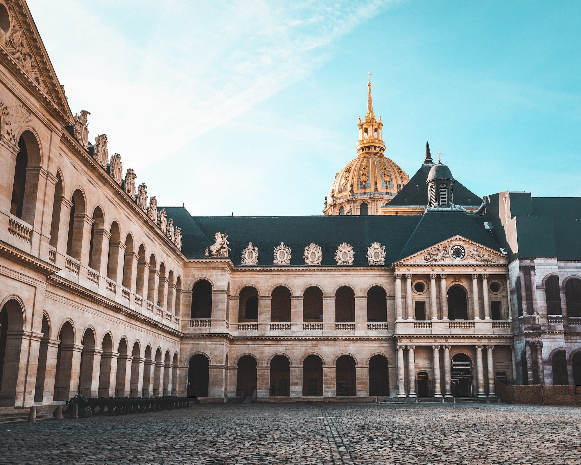 The interior cobblestone courtyard at the Invalides, with the gold dome sticking out the top.
