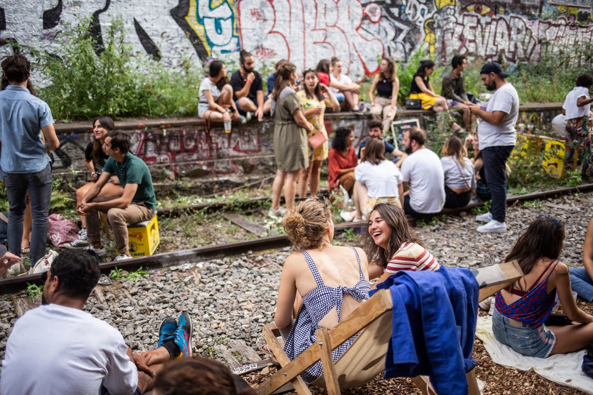 People sitting on the abandoned railway at the Hasard Ludique culture hub in Paris with graffiti-adorned walls.