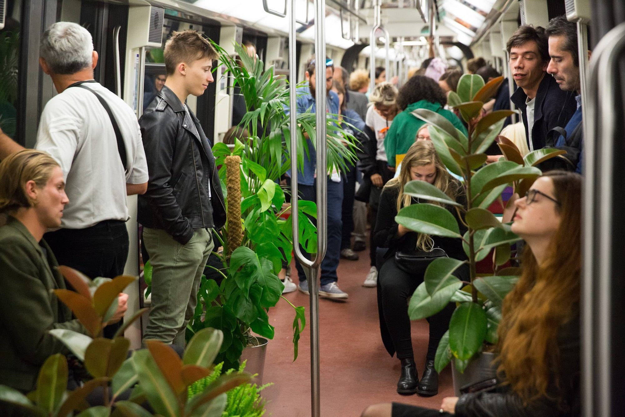 People on the metro which has been adorned with green plants.