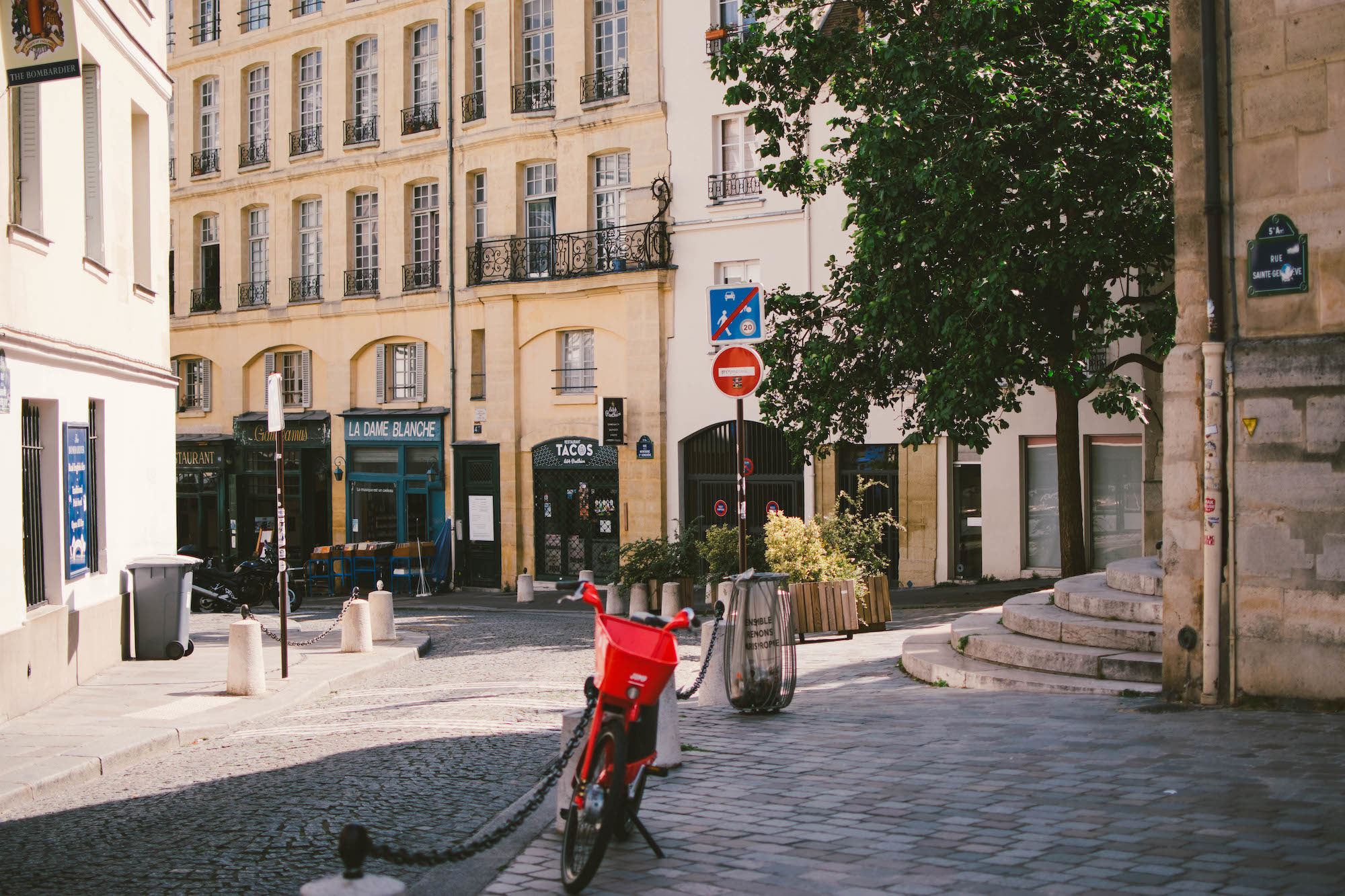 A cobblestone street in Paris with a red bike in the foreground.