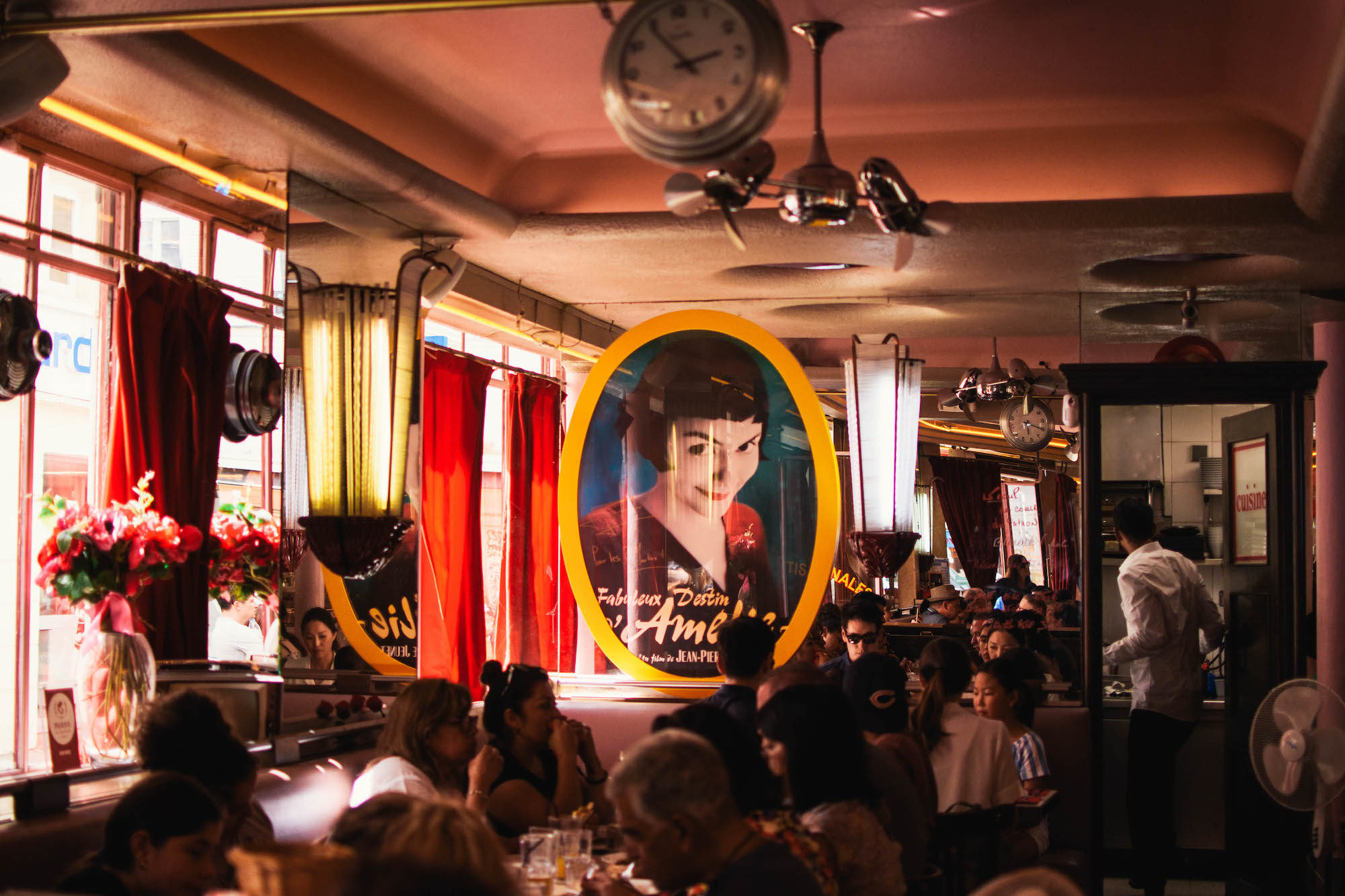"Inside the Café des 2 Moulins, otherwise known as the café in the movie ""Amélie"", with an image of Amélie printed on a glass pane and people sat in booths."