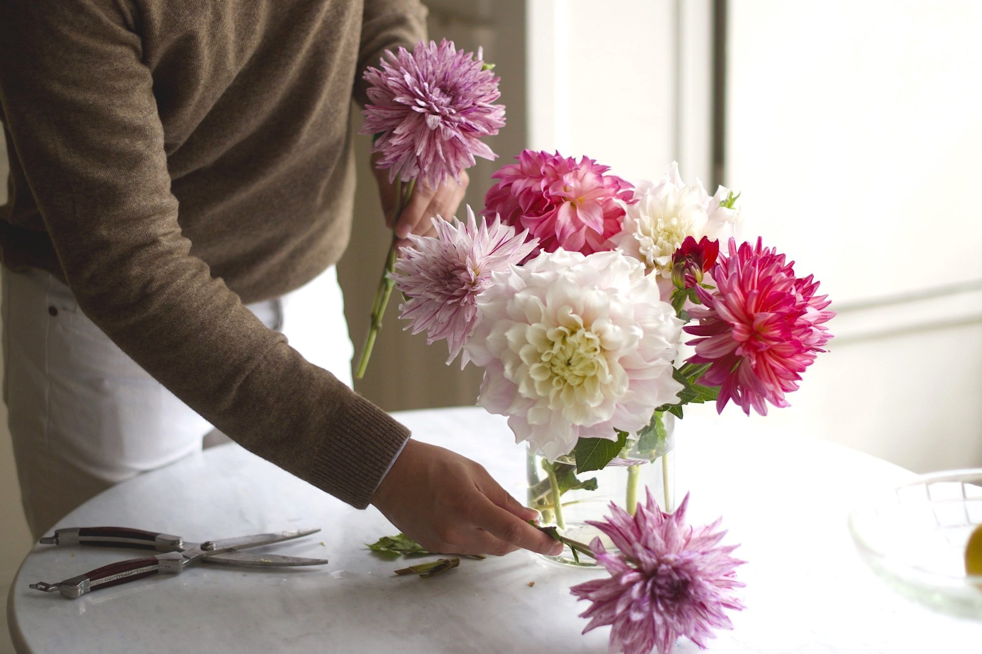 Frank seen arranging delicate pink and purple dahlias at his Paris apartment.