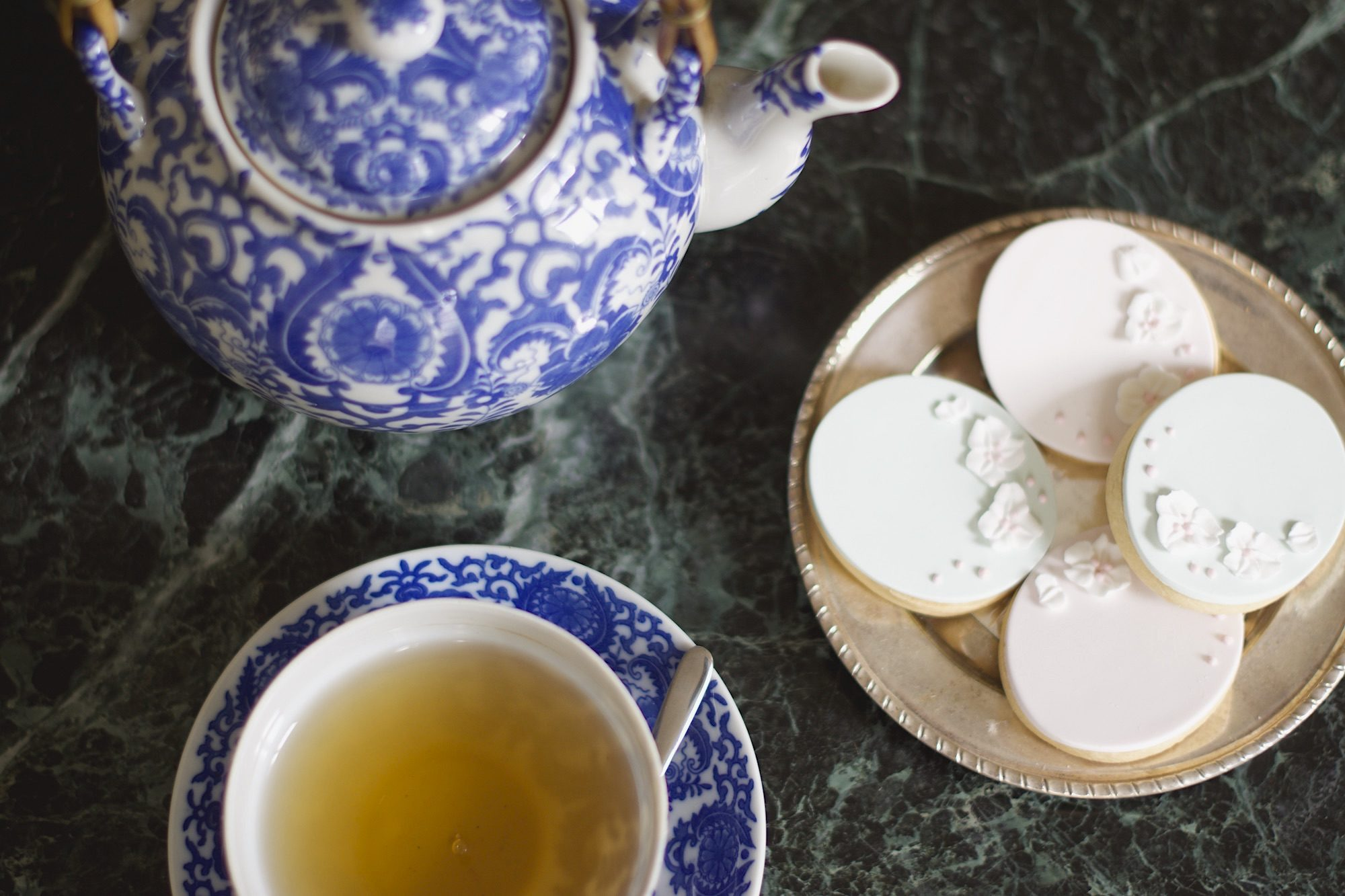 A top shot of a blue and white China teapot and cup with biscuits baked by Frank set on a green marble counter.