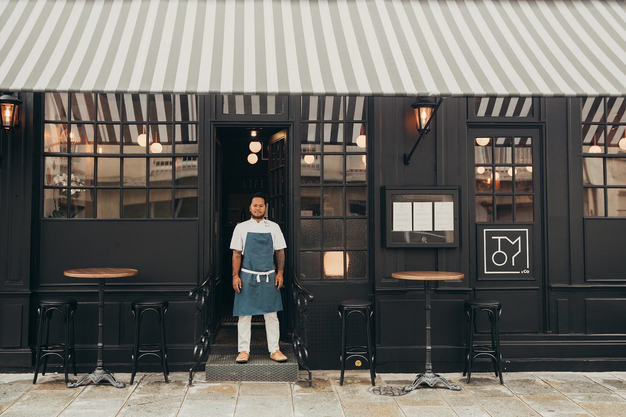 Tomy Gousset, the star chef standing in the doorway of his restaurant Tomy + Co in Paris near the Eiffel Tower.