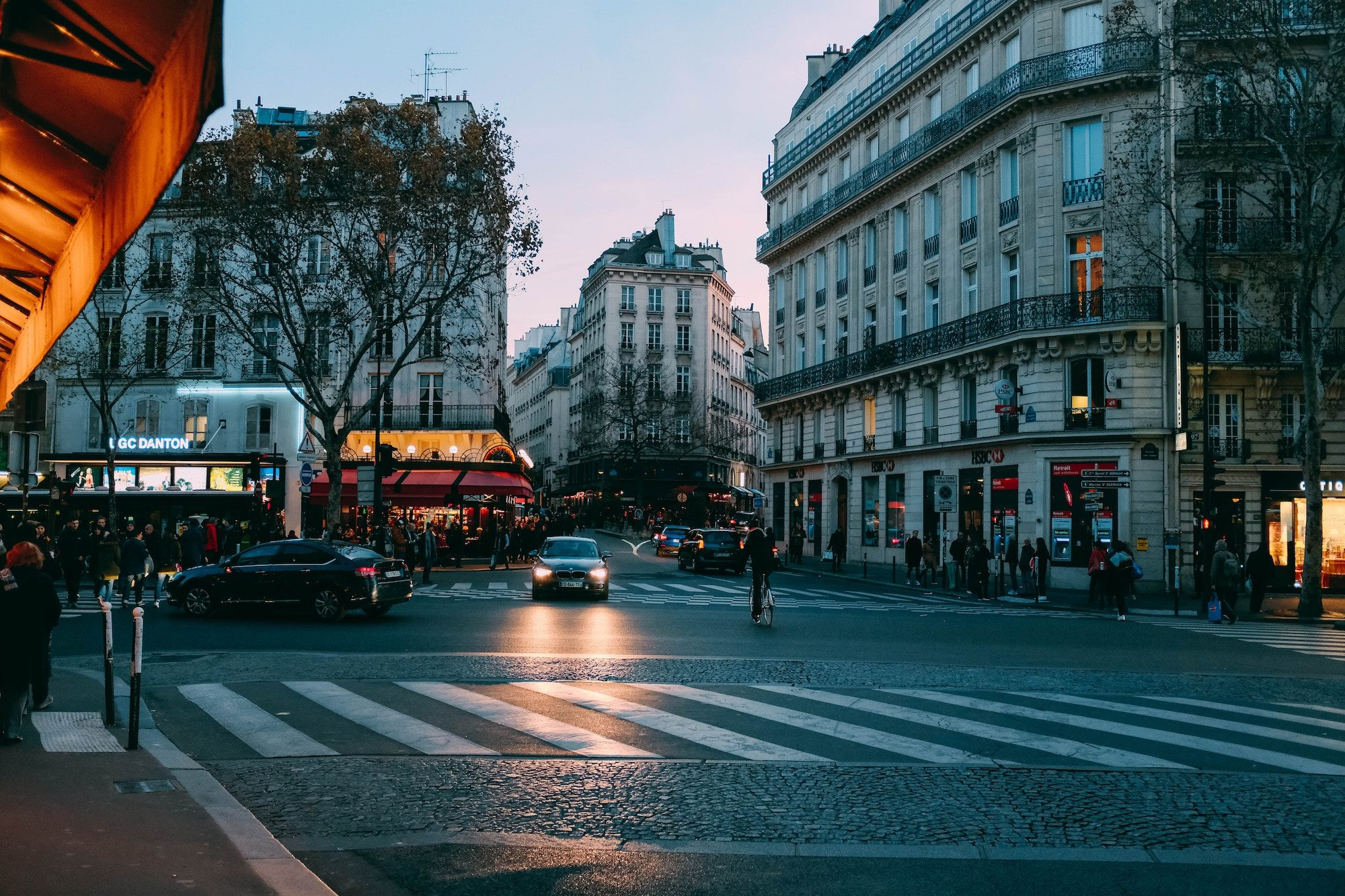An evening street scene in Paris with bluish tinges and warm reddish lights from the surrounding cafés at this crossroads.