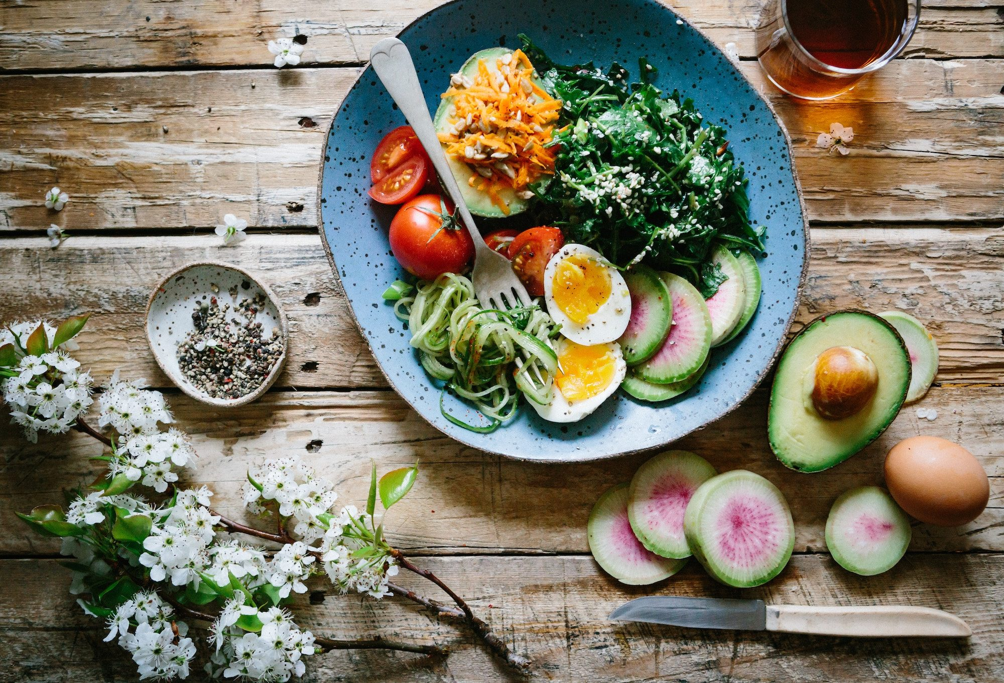 A plate of colorful gluten-free fresh salads and eggs on a wooden table