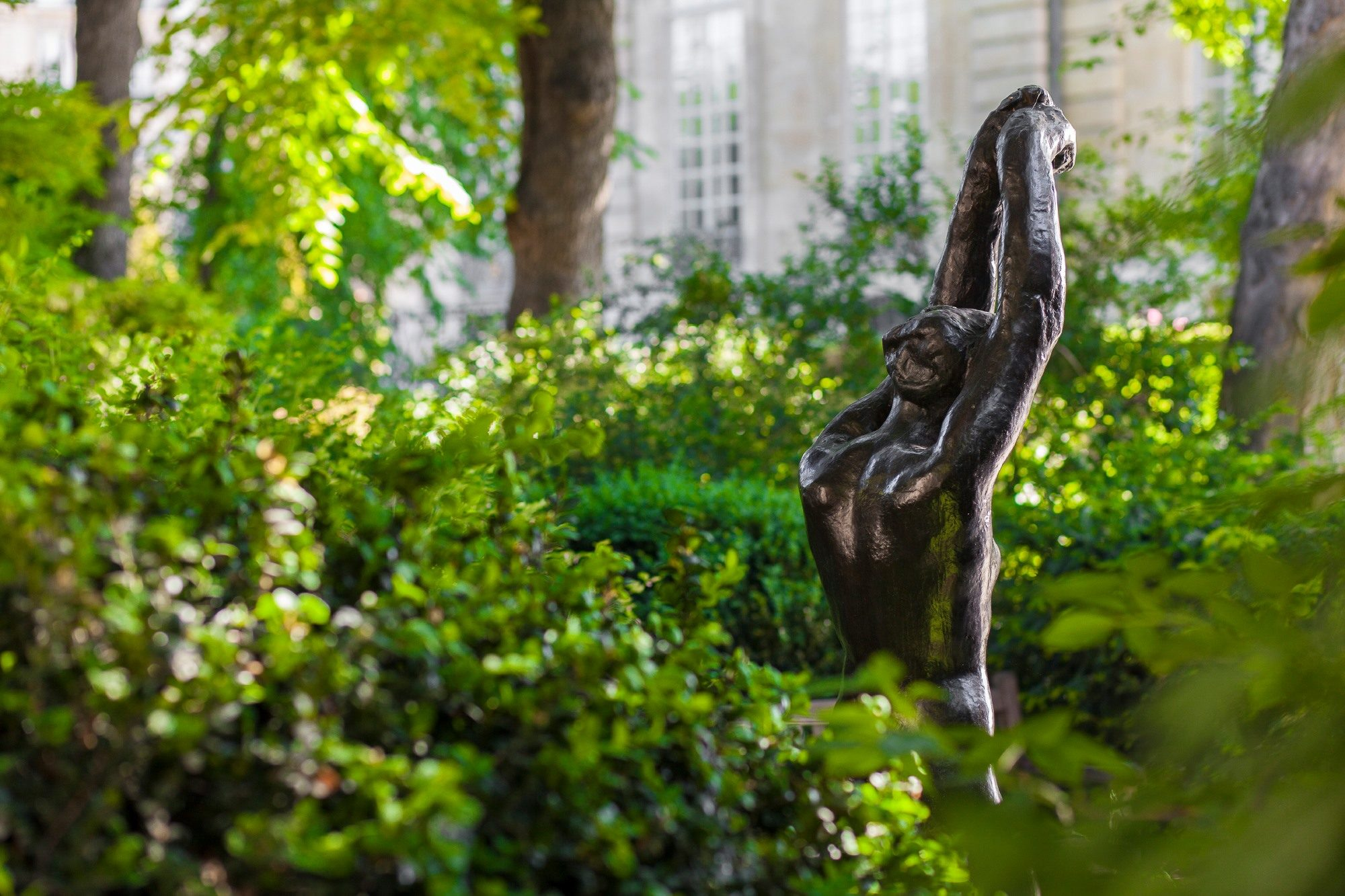 The Rodin Museum gardens with a sculpture of a woman her arms up among the foliage (right).