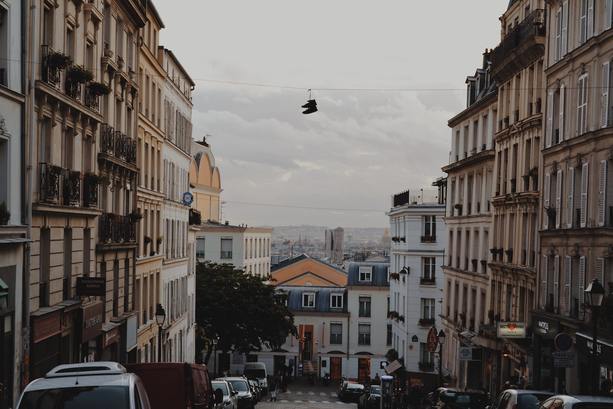 A street scene of Montmartre as the sun sets, which apartment buildings on either side and shoes hanging on street cables in the center.