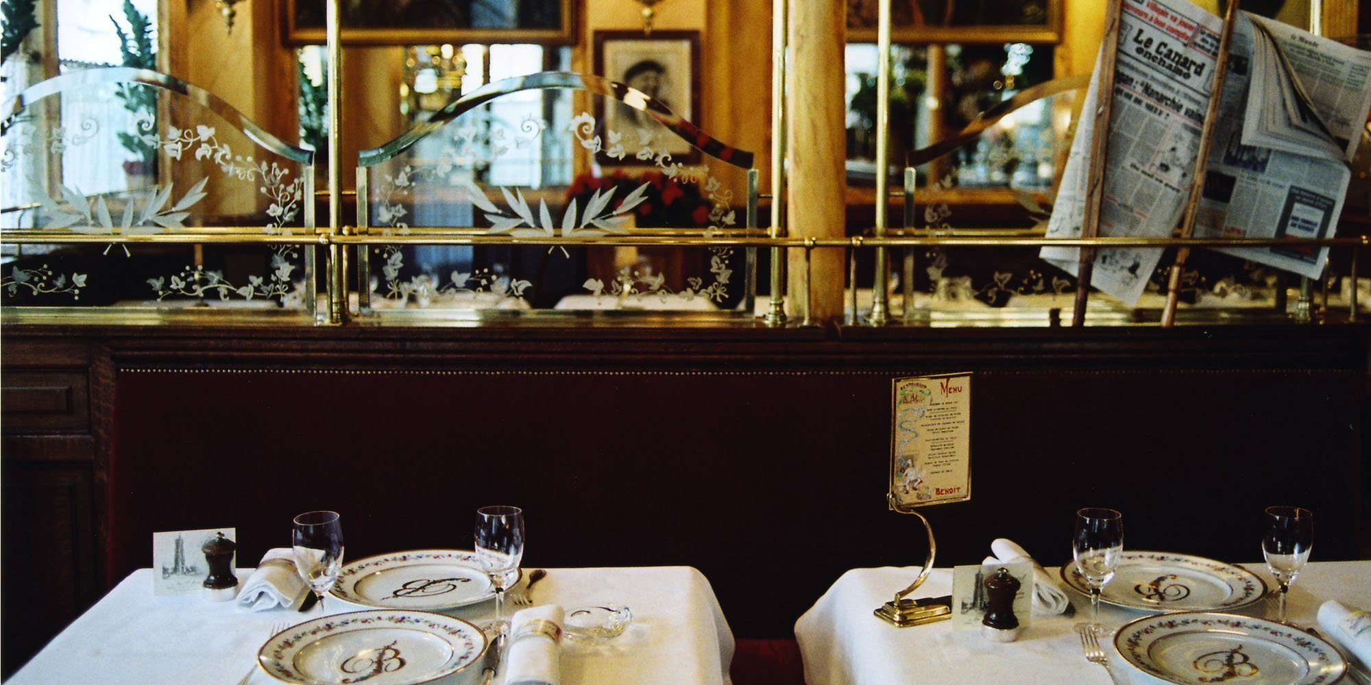 Two tables covered in crisp white table cloths and set for Thanksgiving dinner at Benoit bistro in Paris.