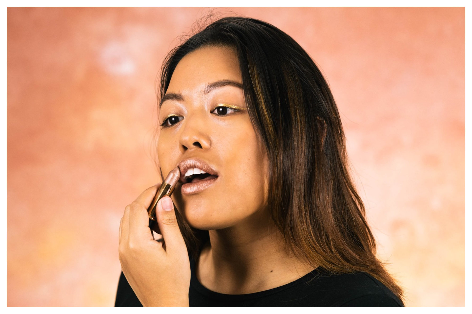 An Asia woman applying a shimmery pink lipstick from organic store Naturalia.