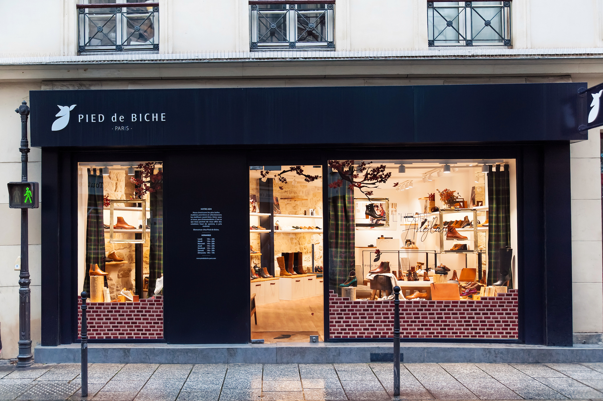Petrol blue exterior of Pied de Biche stylish French shoes shop brand as night is falling.