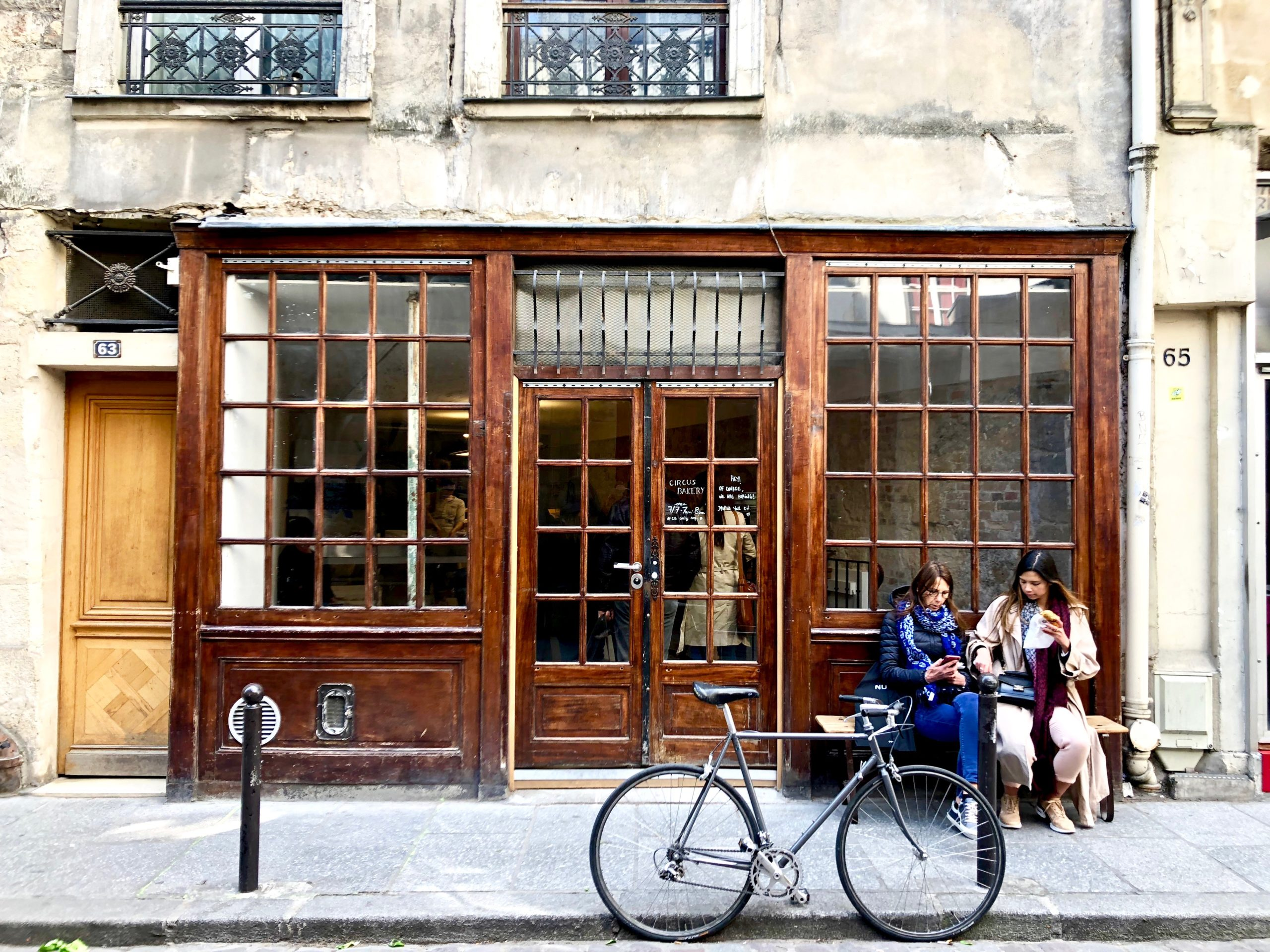 The old wooden exterior of Circus Bakery in Paris with two women sitting outside on a bench.
