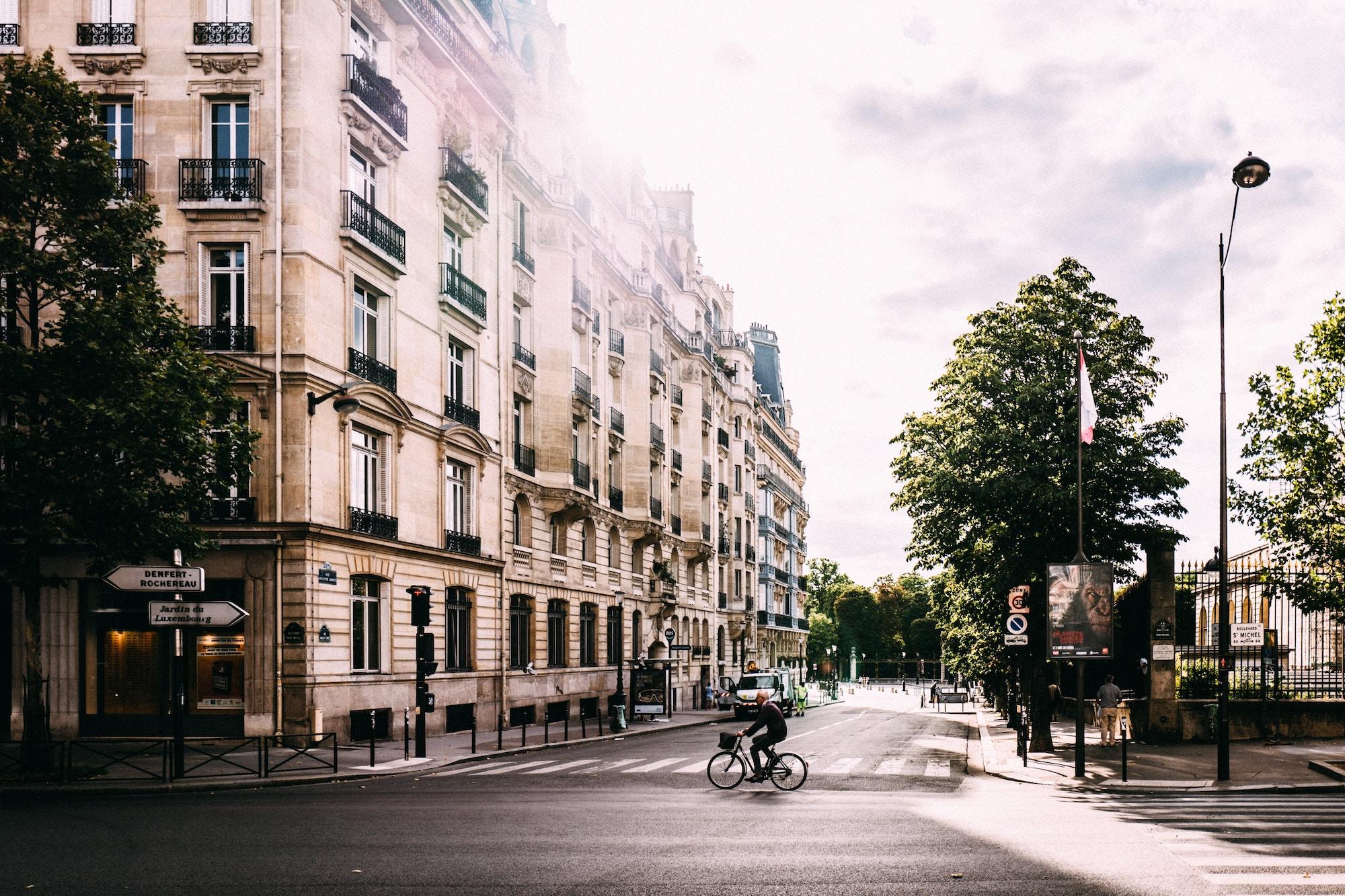 A cyclist rides across an empty street in Paris as the sun peeks from behind a classic Haussmann apartment building.