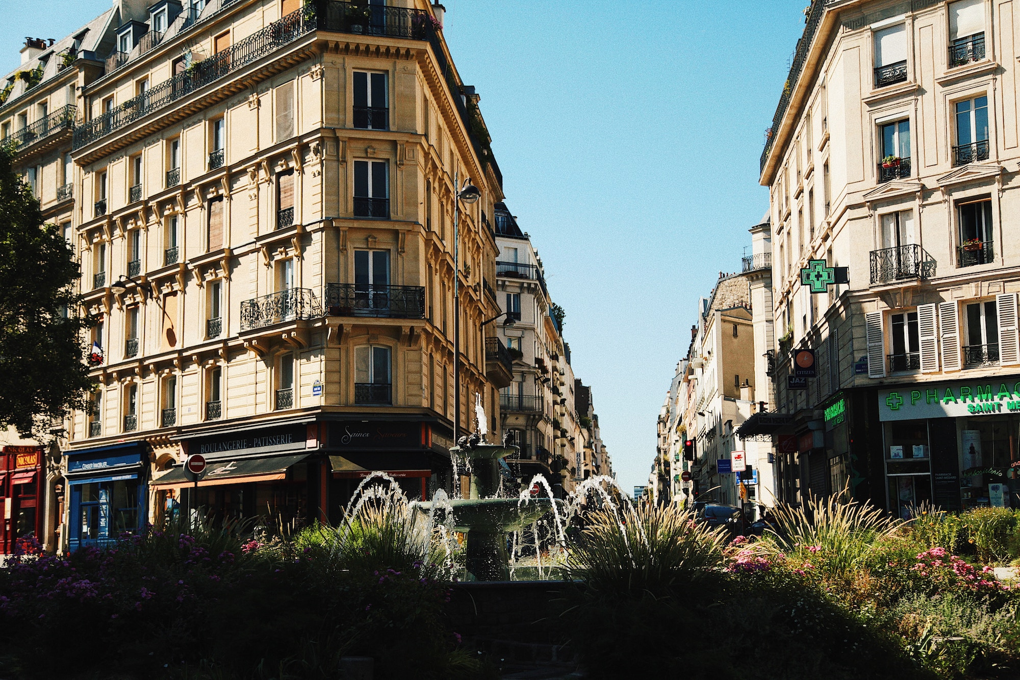 On a bright, sunny day, a fountain trickles in a Parisian square as the apartment buildings are bathed in sunlight.