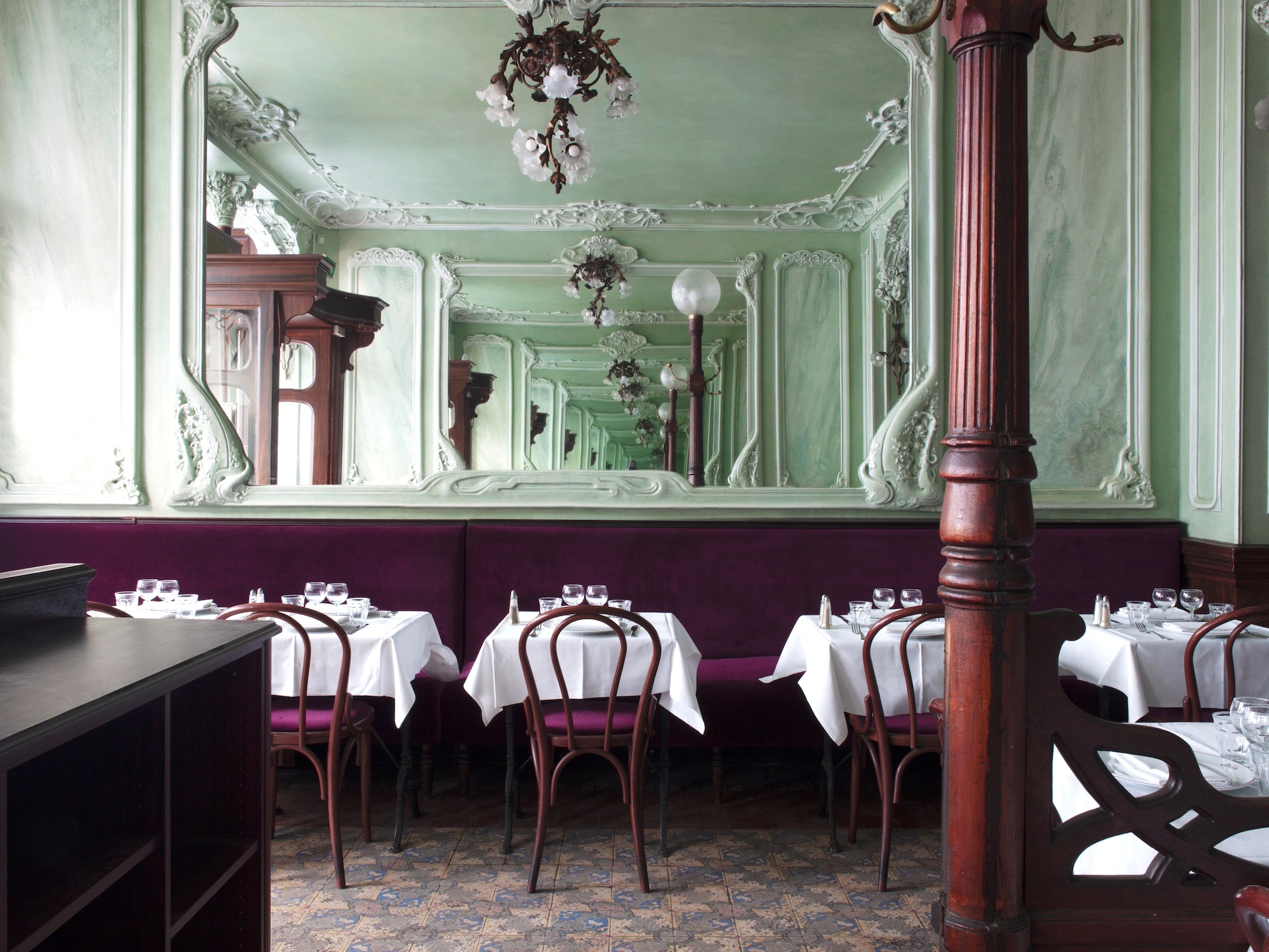 The art nouveau interior of Bouillon Julien restaurant in Paris. Pale green walls with a large mirror in the middle, chandeliers, maroon bench seat and chairs with tables with white table cloths and wine glasses.