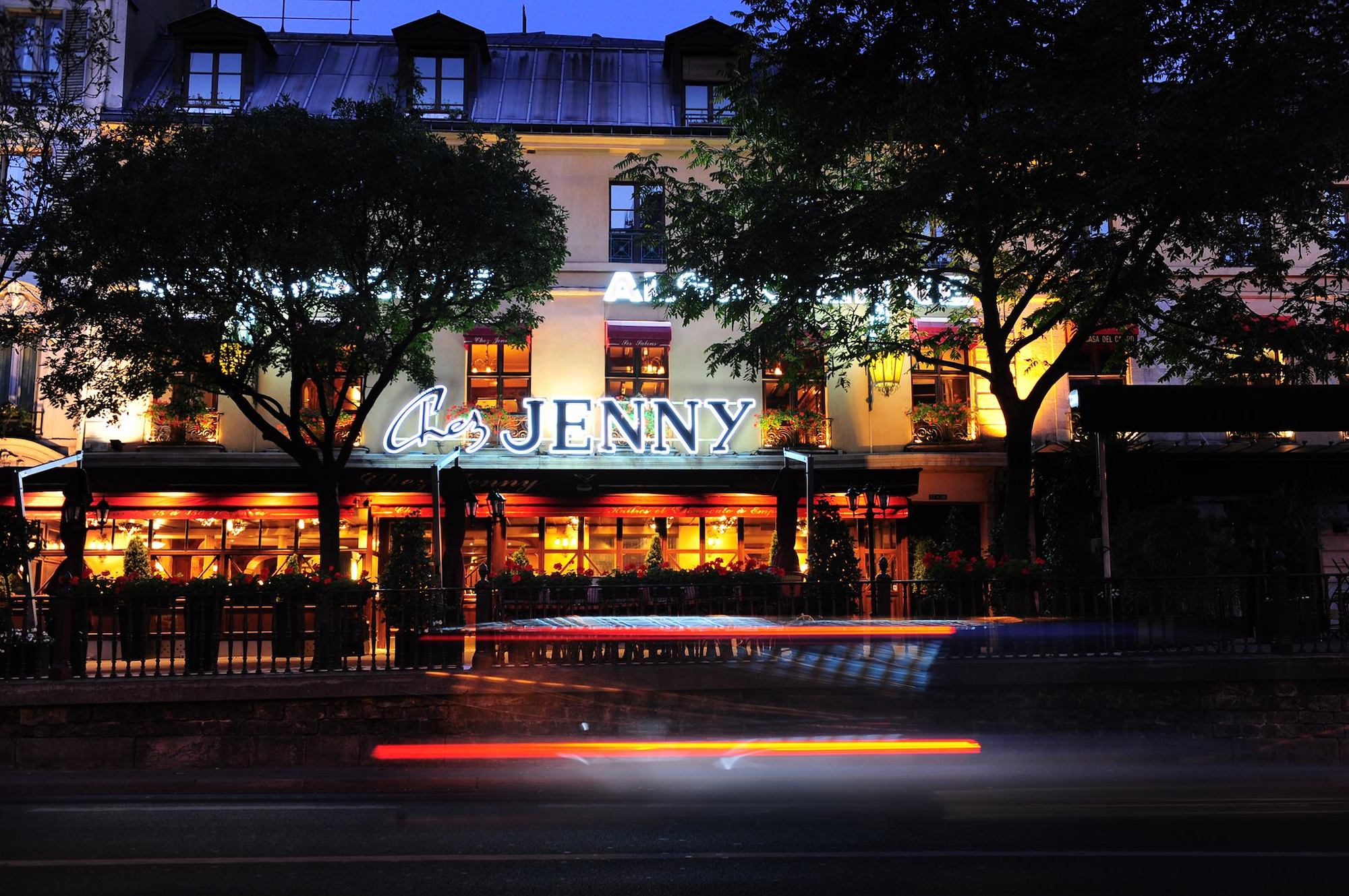 The exterior of the restaurant Chez Jenny in Paris at night time, with a large white neon sign saying Chez Jenny and streaks of light in front from a passing car.