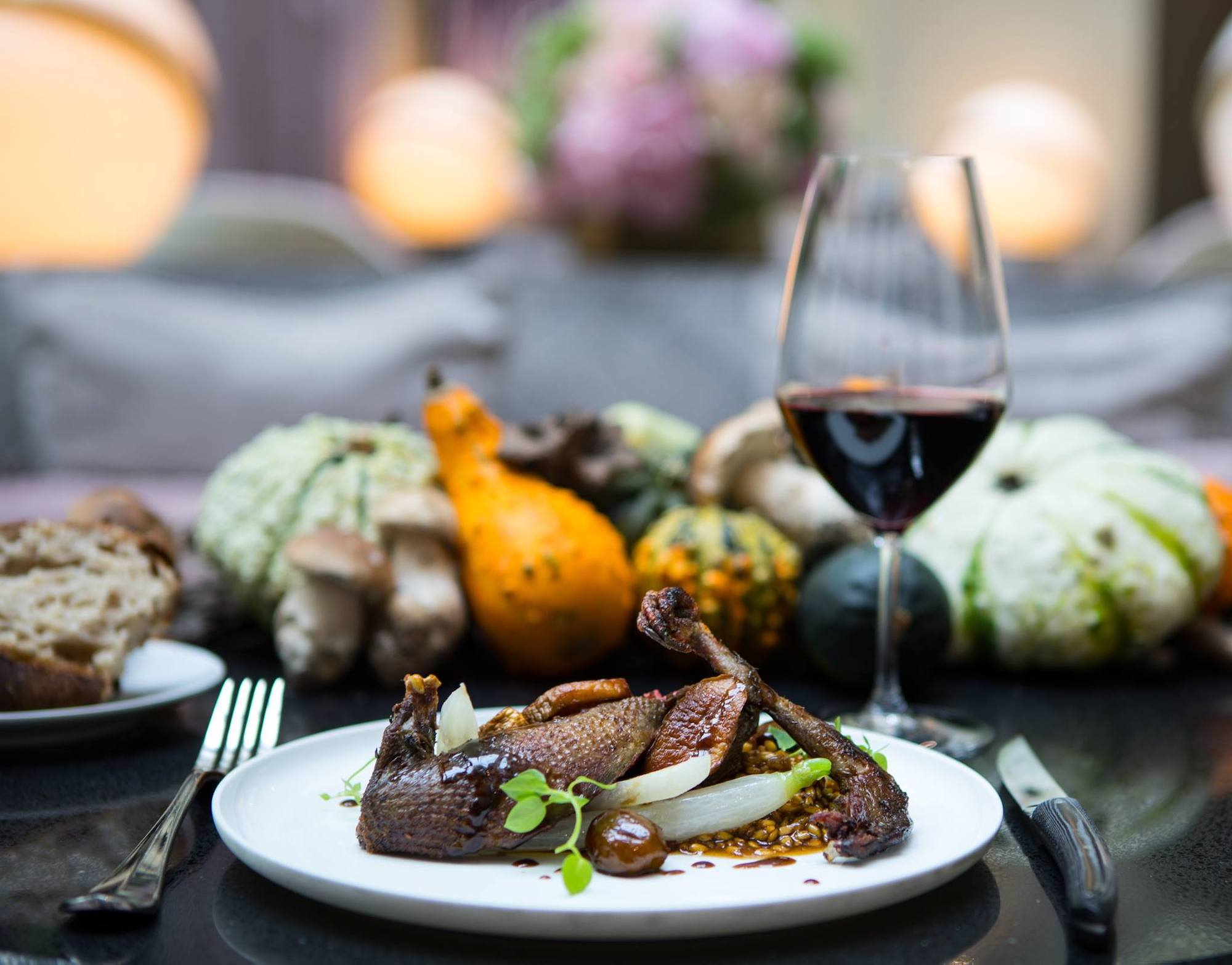 A white plate with roast pigeon, wheat risotto, turnip and chestnut, with cutlery on either side and a glass of red wine in the background, some bread, and an assortment of decorative squash.