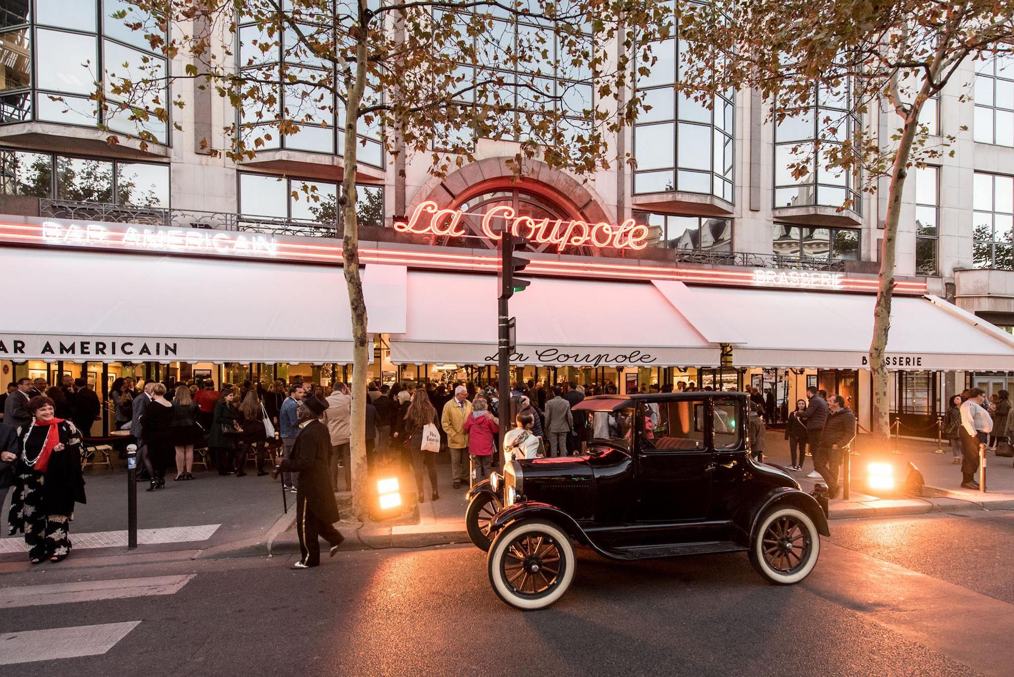 The exterior of La Coupole restaurant in Paris. A neon sign saying La Coupole, a white terrace shade, people standing in the terrace and an old fashioned black car parked out the front.