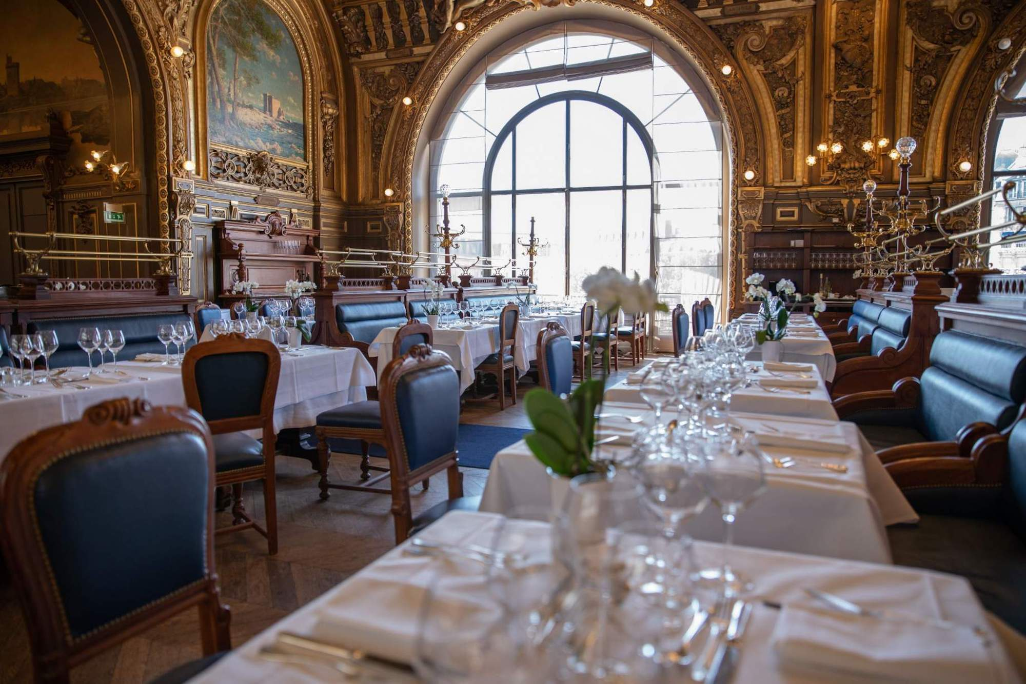 The opulent interior of the restaurant Le Train Bleu in Paris, tables covered in white tablecloths with white serviettes and wine glasses, blue upholstered seats, the walls have painted frescoes and carved gold detailing.