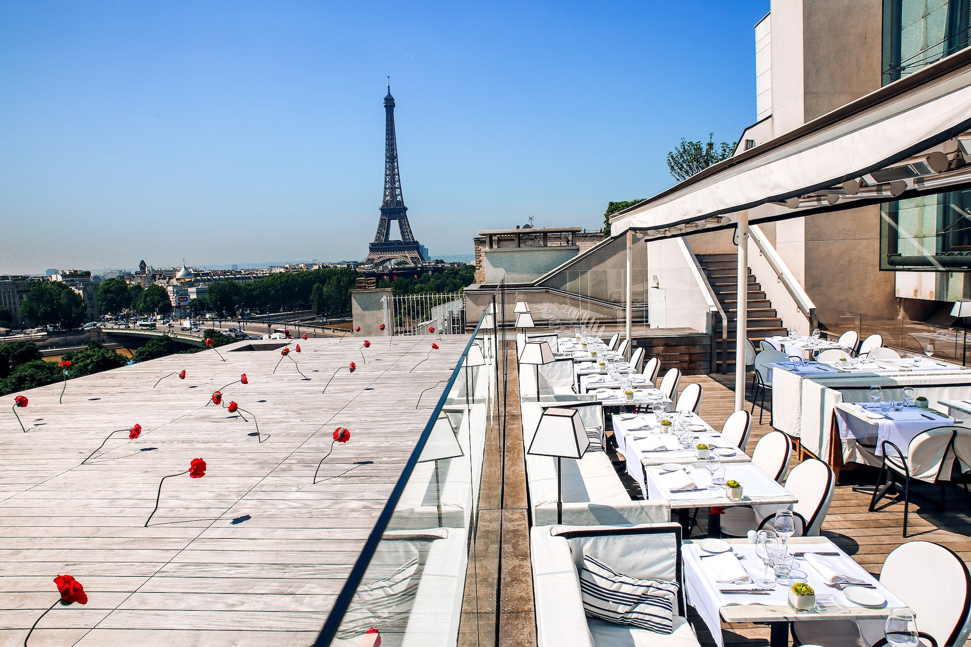 The outdoor terrace of the restaurant La Maison Blanche in Paris, with white tables and chairs, a wooden patio with an art installation of red poppies, and a view of the Eiffel Tower against a blue sky.