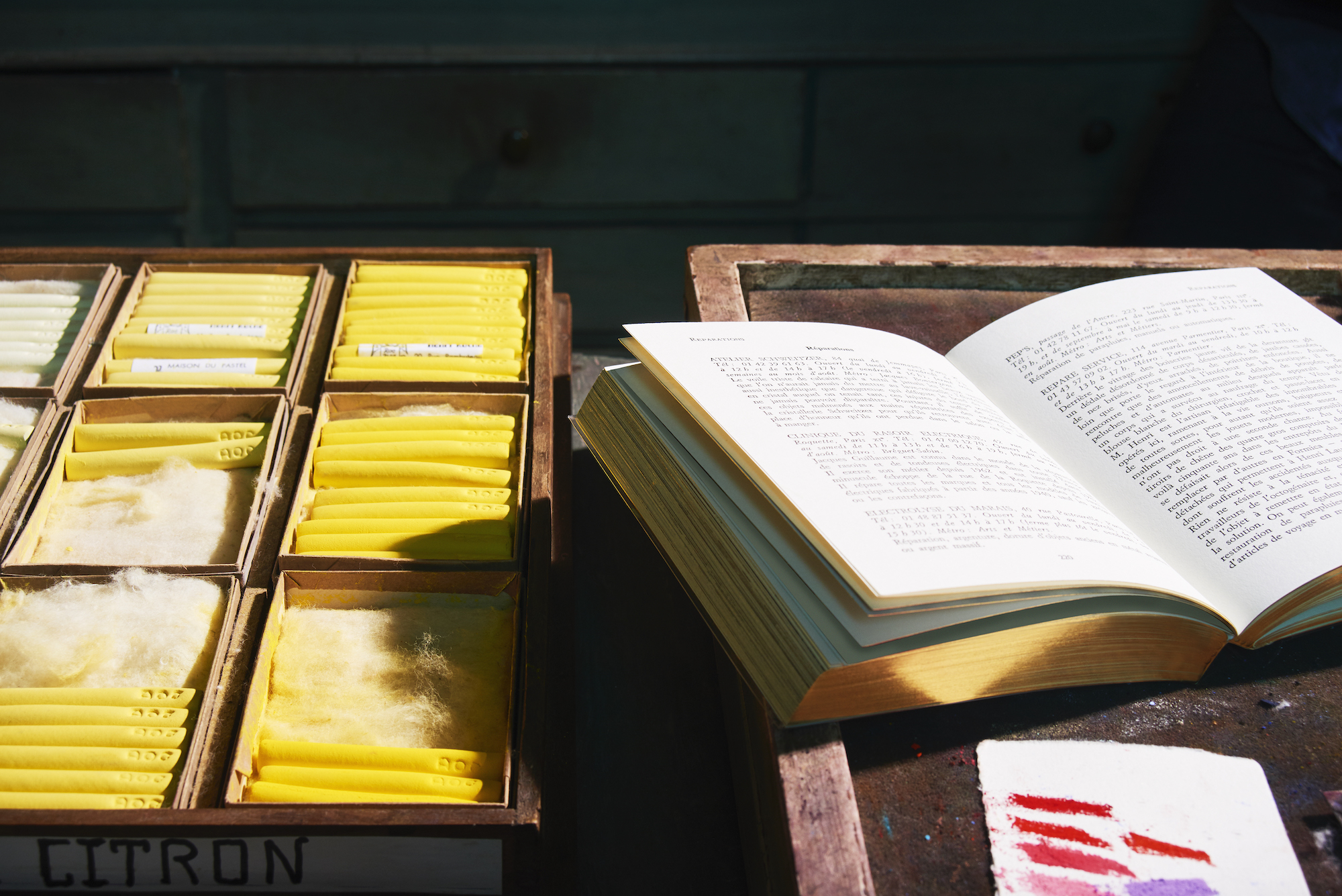 A book by Astier de Vilatte, with gold trim, opened on a wooden tray, outside in the sun.