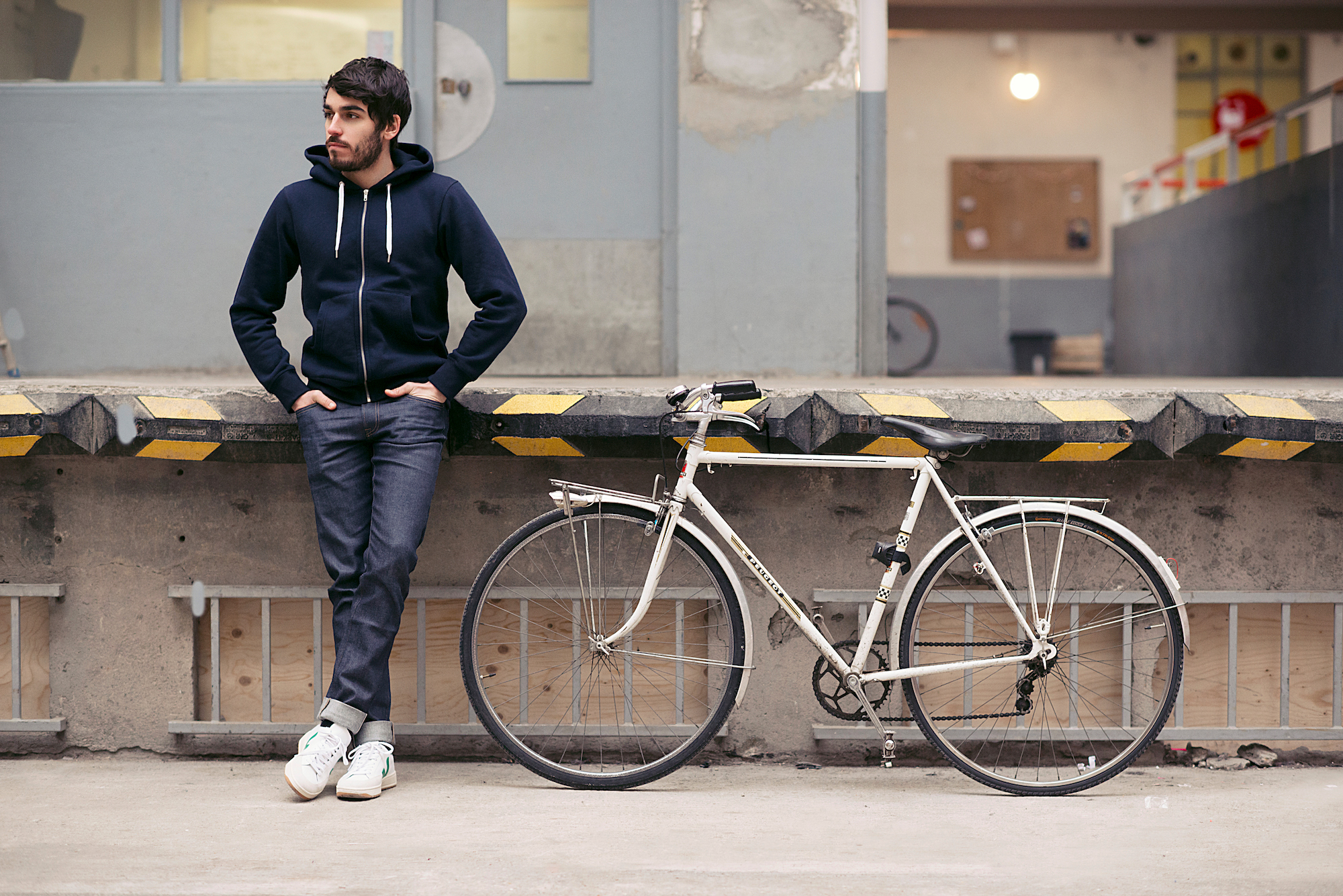 A man casually leans against a loading dock, legs crossed and hands in his pockets, looking away from the camera. He wears a navy hoodie, and cuffed jeans by the ethical French fashion brand Loom.