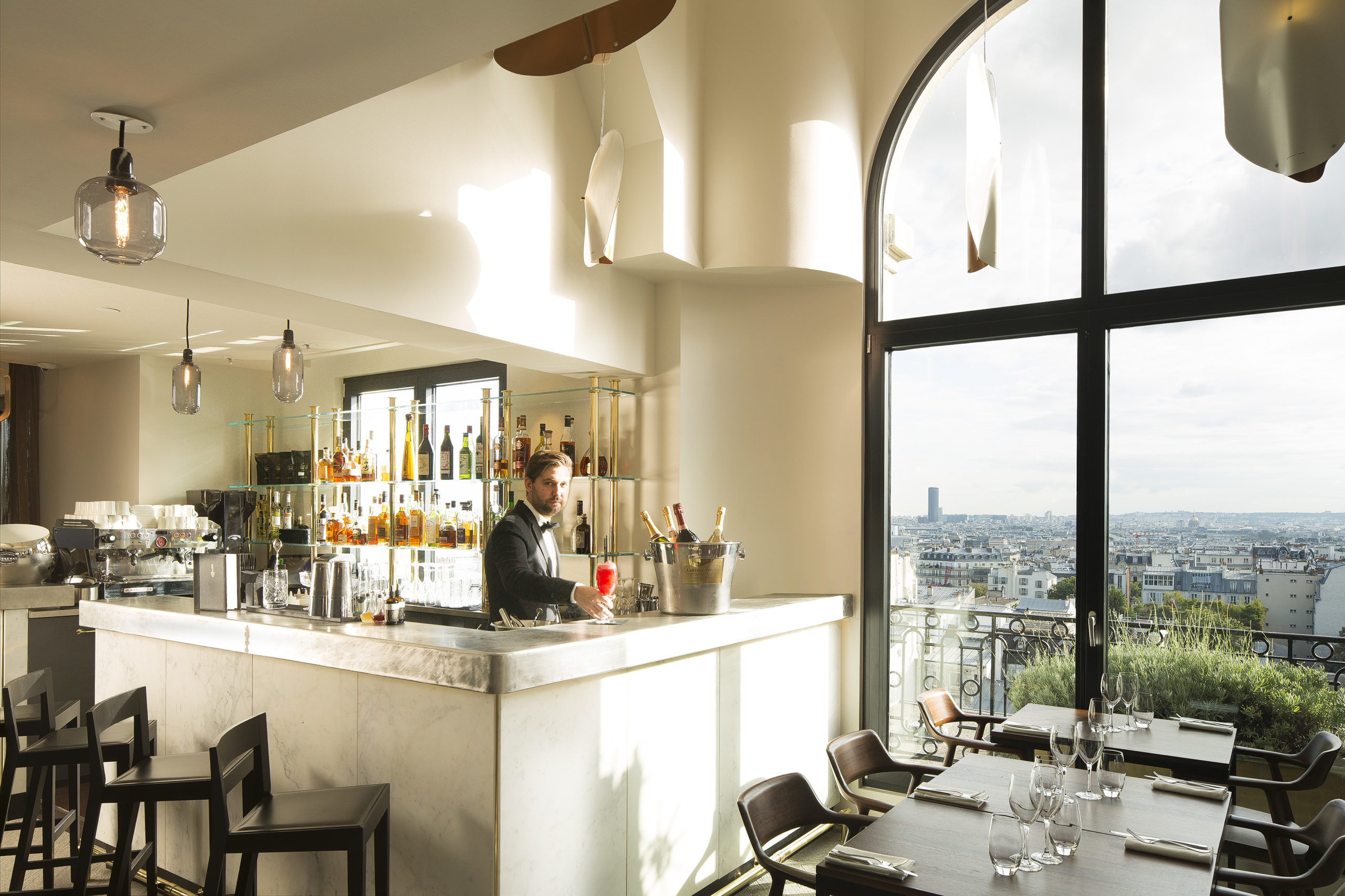 Bartender standing behind a white bar looking over Paris