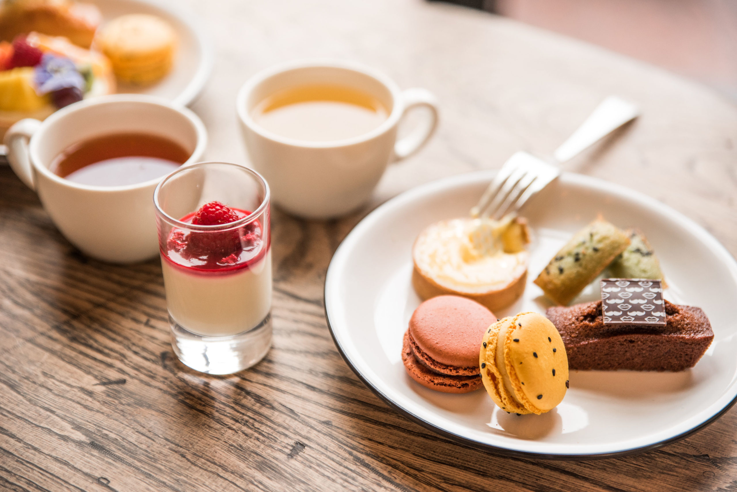 Macarons, a mini lemon tart, and financiers sit next to panna cotta and piping hot cups of tea.