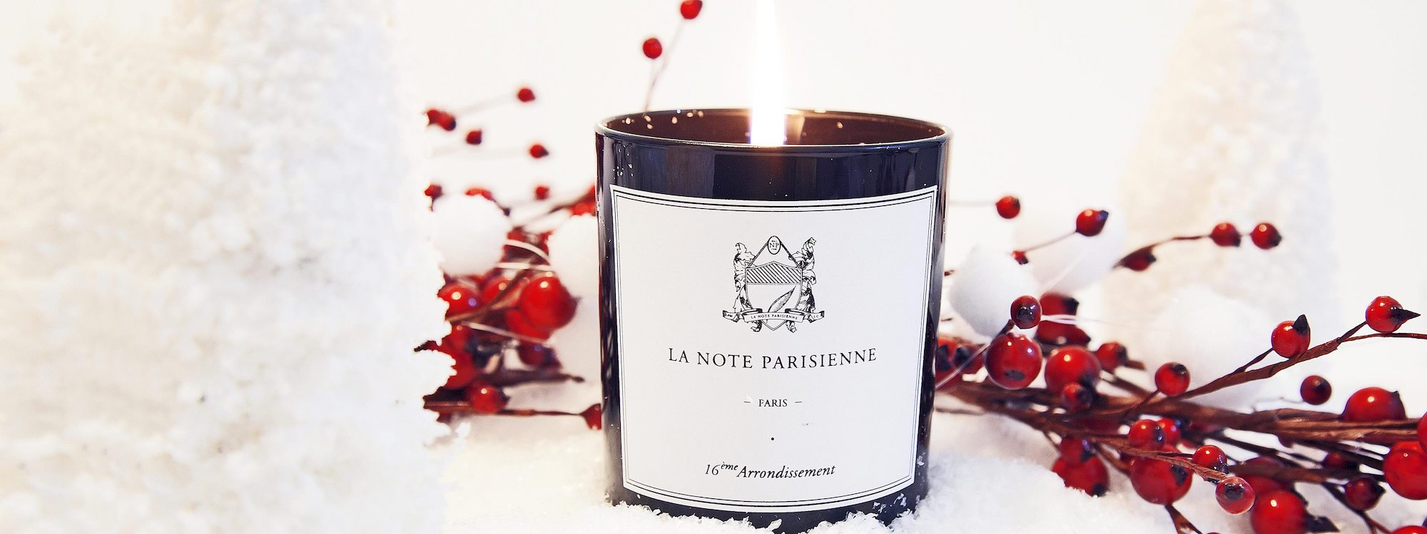 A lit candle from La Note Parisienne in a dark glass container with a black and white label. It is sat within a snowy, white Christmas setting with red berry sprays just behind it.