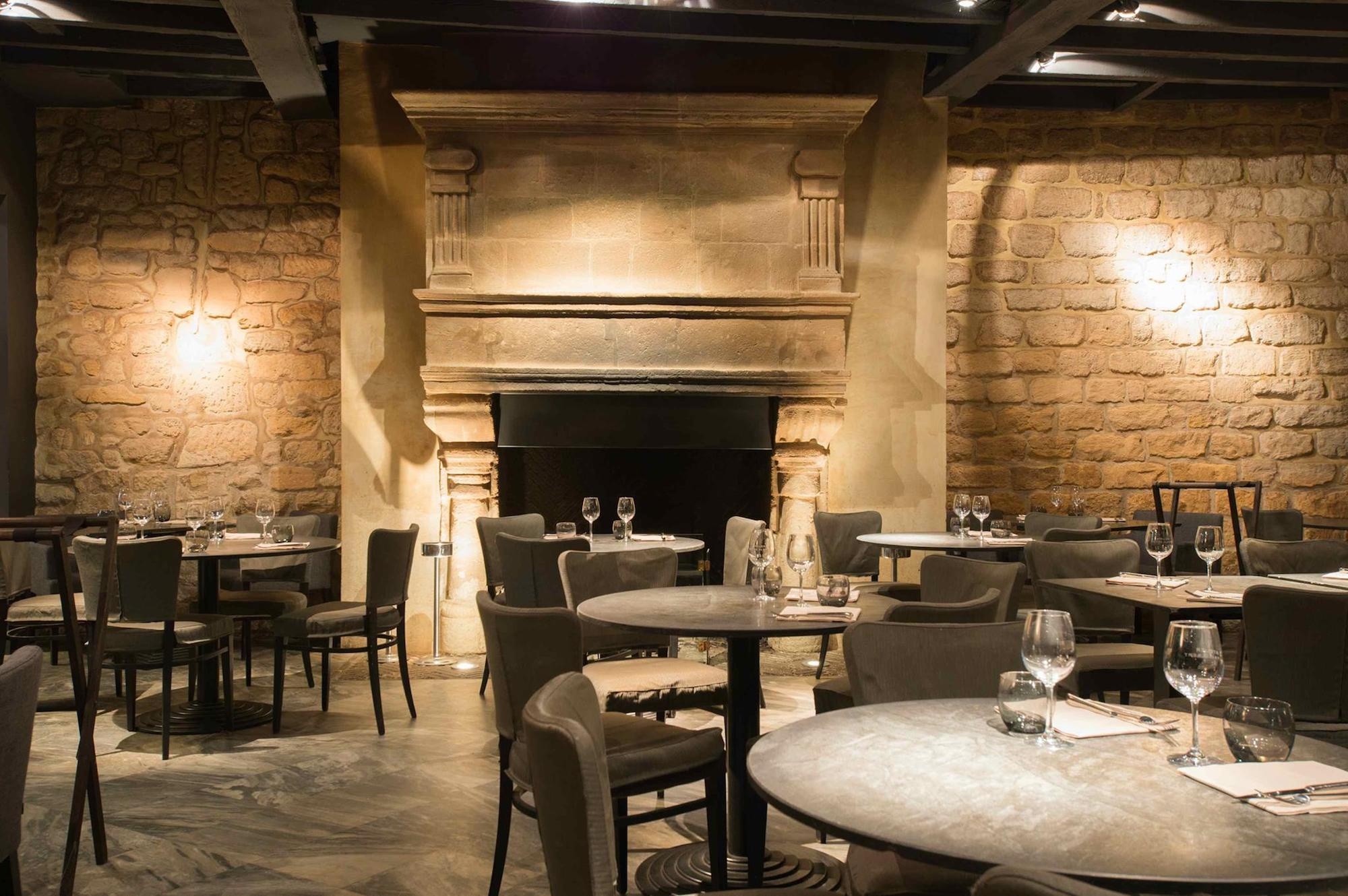 The chimney room of Atelier Maître Albert features an imposing stone fireplace and open kitchen. Diners can enjoy fireside meals in this Left-bank establishment opposite Notre Dame.
