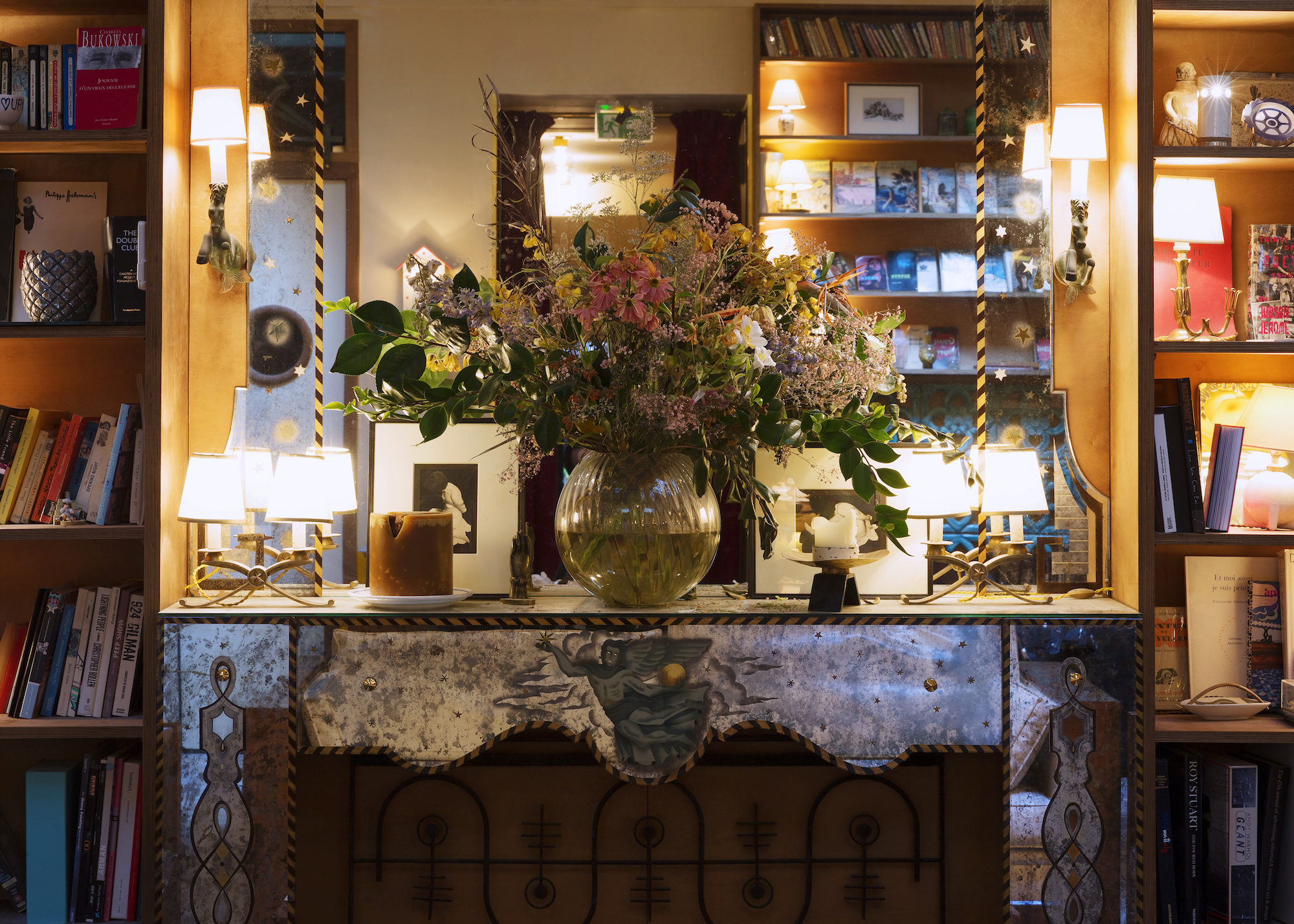 The bohemian salon of the Hôtel Grand Amour in Paris' 10th arrondissement welcomes guests to peruse its overflowing bookshelves and stand by the fire.