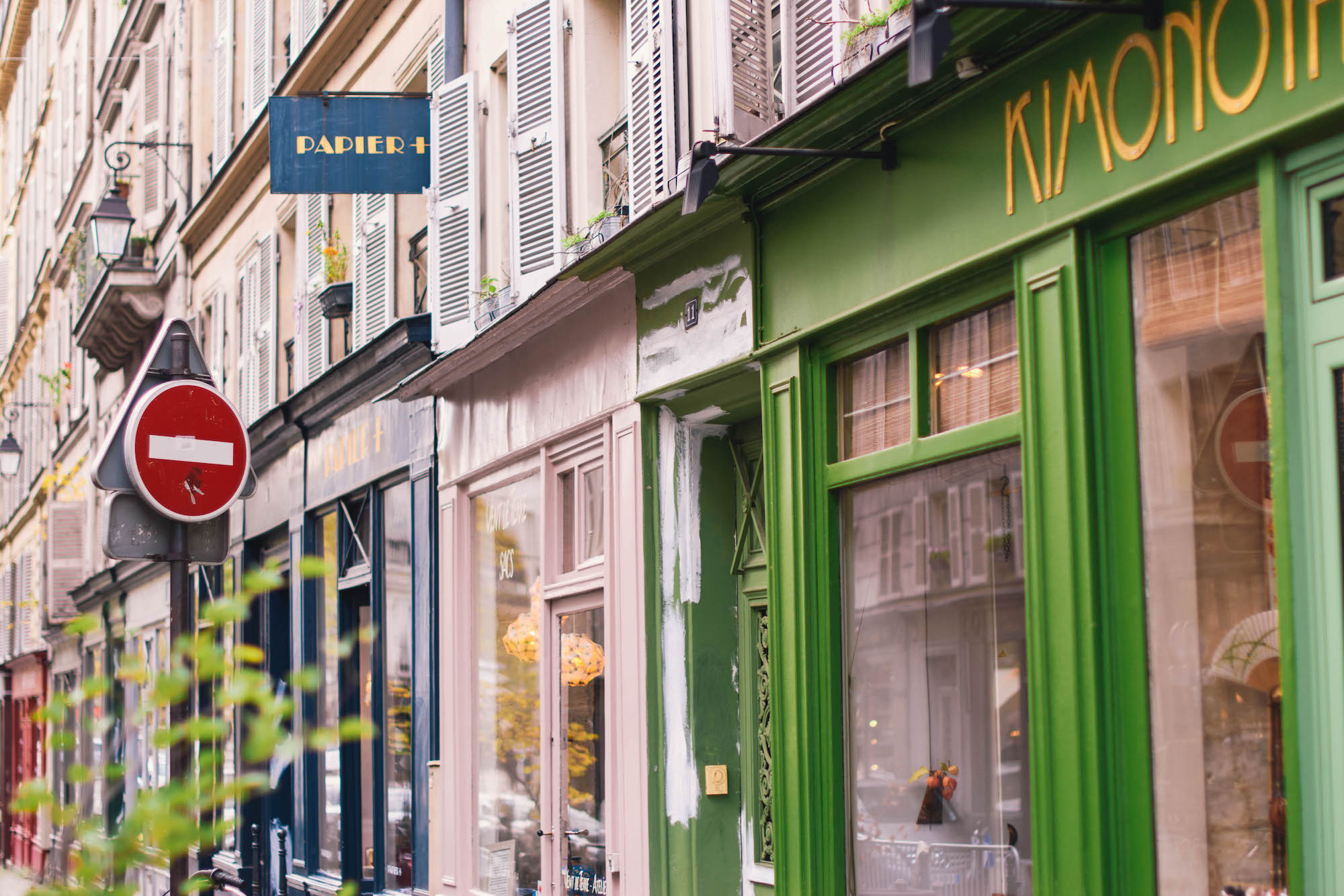 Colorful shops on a calm Paris street wait for buyers to trickle in on a sunny fall day.