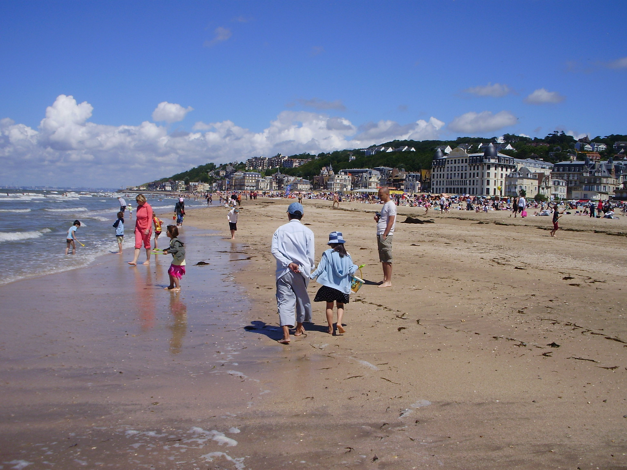 Beachgoers enjoy an afternoon stroll in Deauville, dipping in and out of the playful waves.