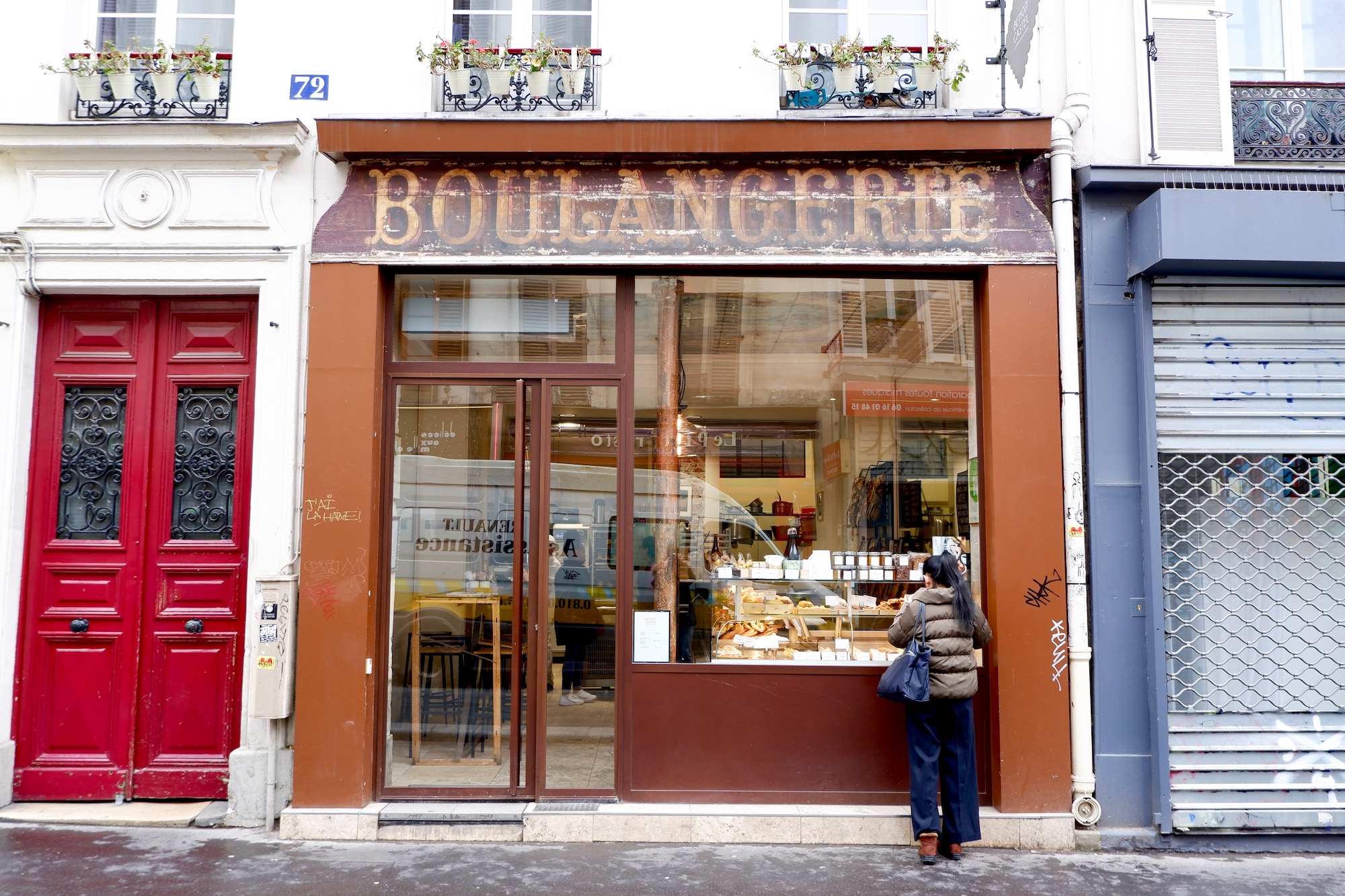 The facade of a boulangerie. There is a vintage sign above the windows. A woman is looking in the windows at the pastries on display.