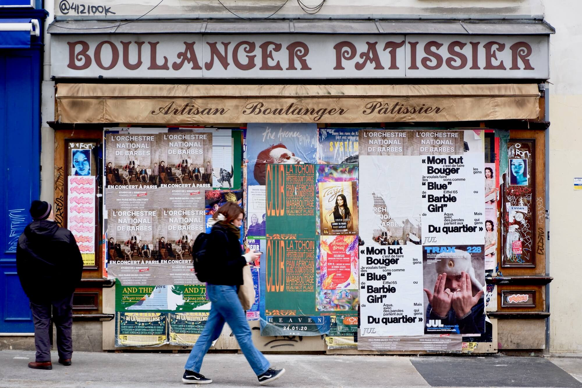 An old boulanger/patissier that has been covered in promotional music posters. An elderly man to the left is looking up at the posters while a young woman is walking past, slightly blurred.