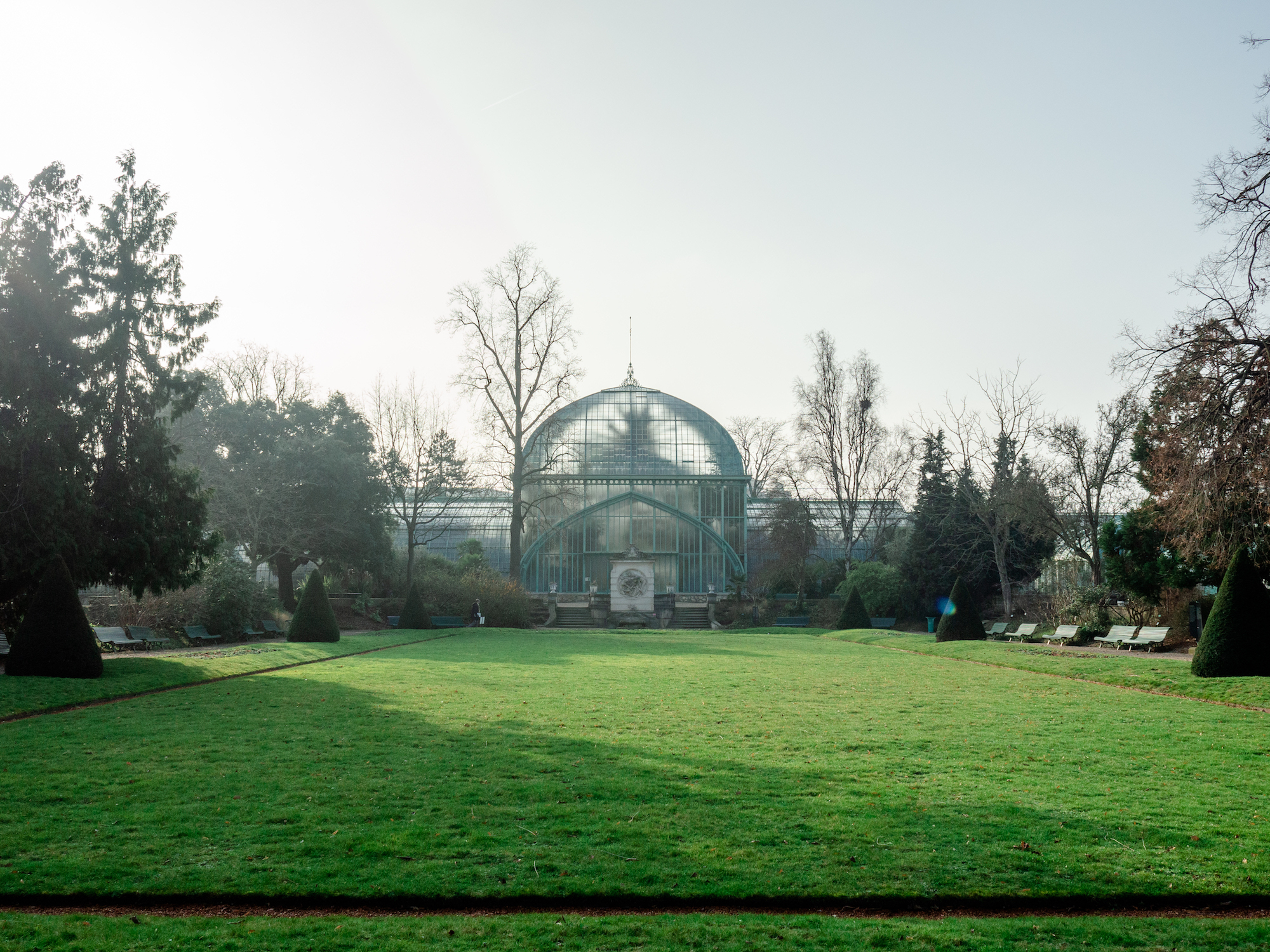 The greenhouse, called the Serres d'Auteuil, in Paris' 16th arrondissement, is illuminated by the sunrise. Sunlight streams through the pointed dome, spilling onto the lawn that leads to the entrance.