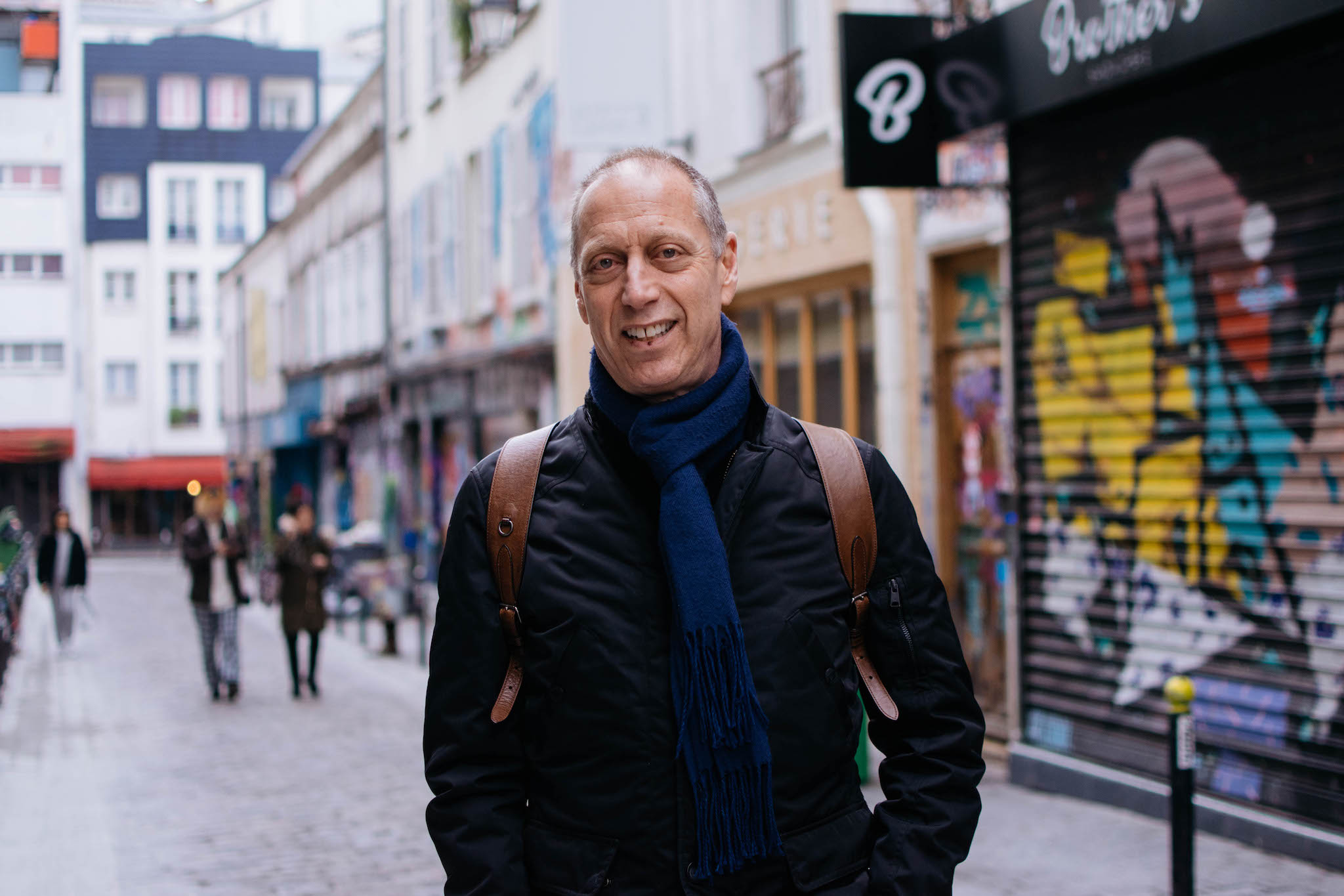 A portrait of David Lebovitz standing with a smile in the middle of a street in Paris' diverse Bellville neighborhood.