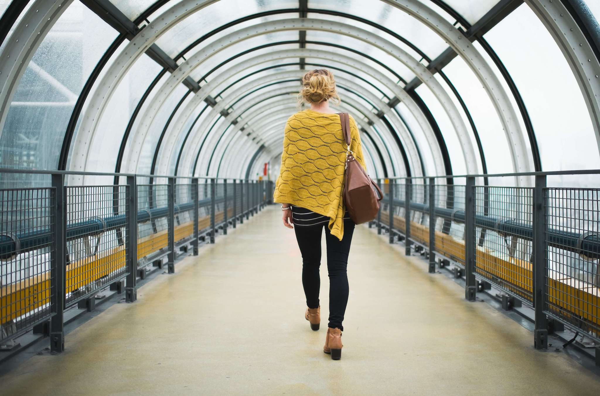 A blonde woman wearing a yellow poncho, black jeans, and brown boots and handbag is walking down a glass cylindrical corridor in Centre Pompidou. The photo is taken from behind.