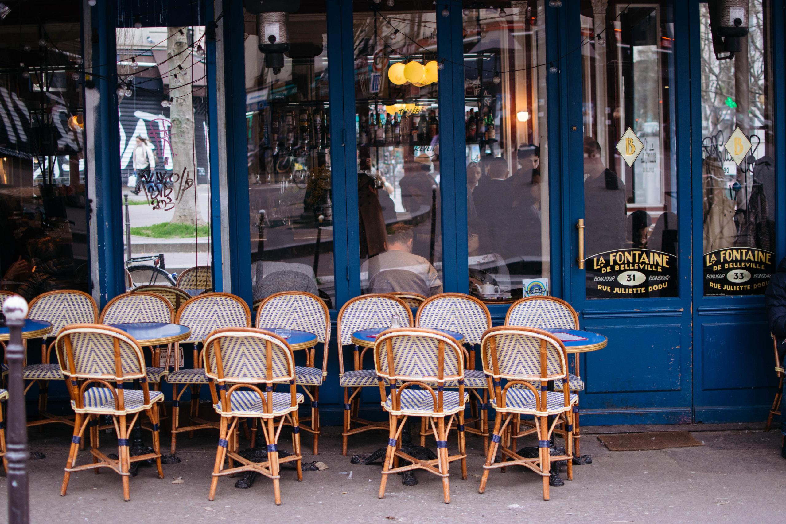 Café tables and chairs sit outside La Fontaine de Belleville, a french coffee shop in Paris' 10th arrondissement.