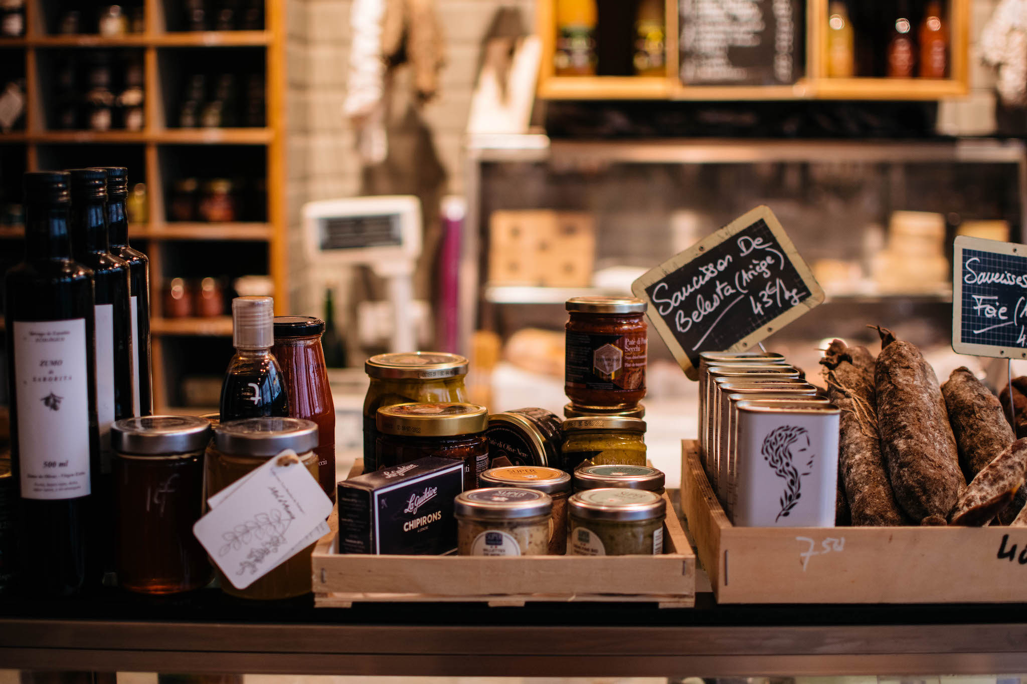 An array of apéritif items, including spreads and sausages, sit on a counter at Le Petit Grain, a zero-waste bakery in Paris.