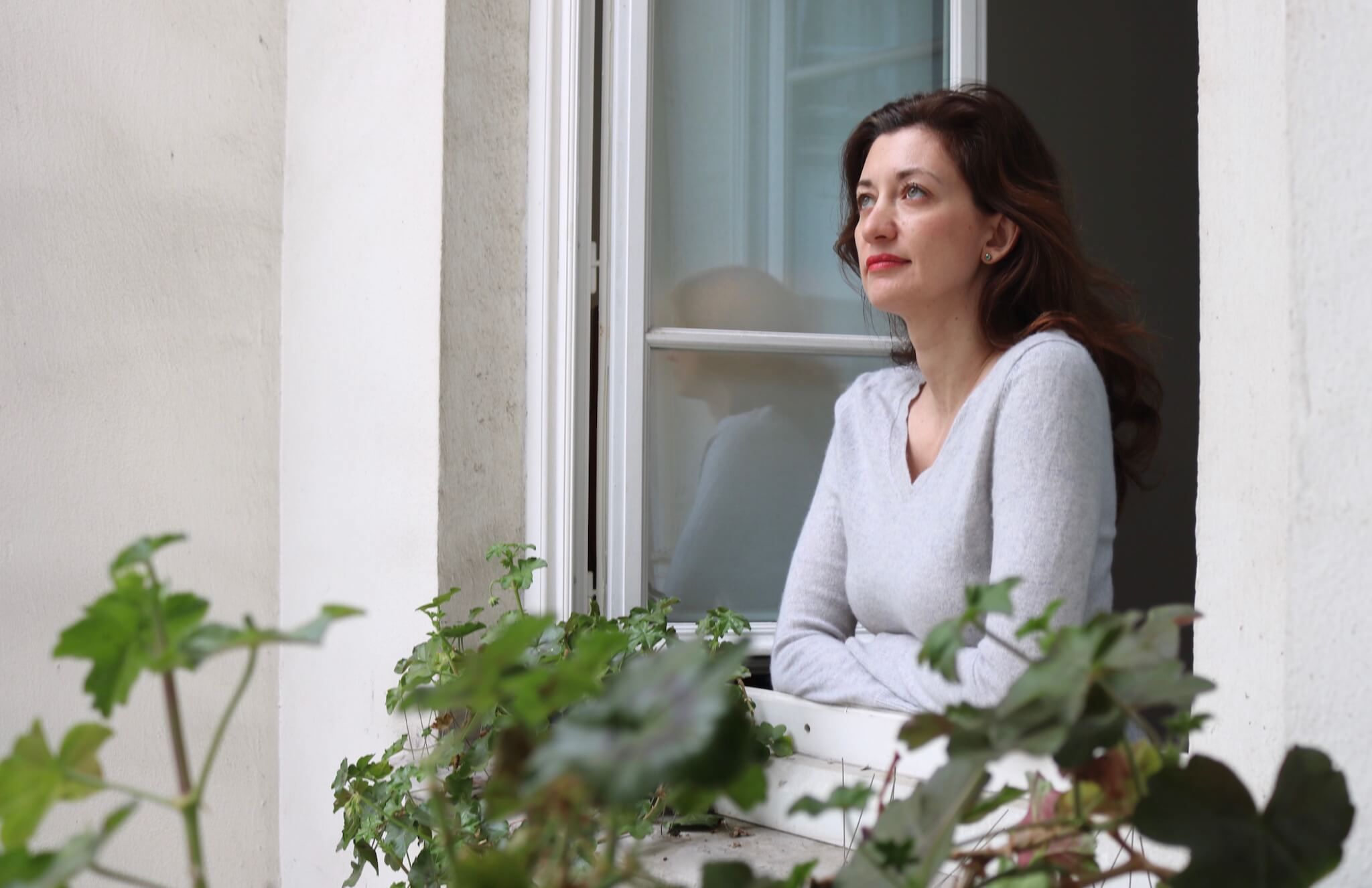 Kasia stands at her window in Paris, looking out at the view from her Marais apartment